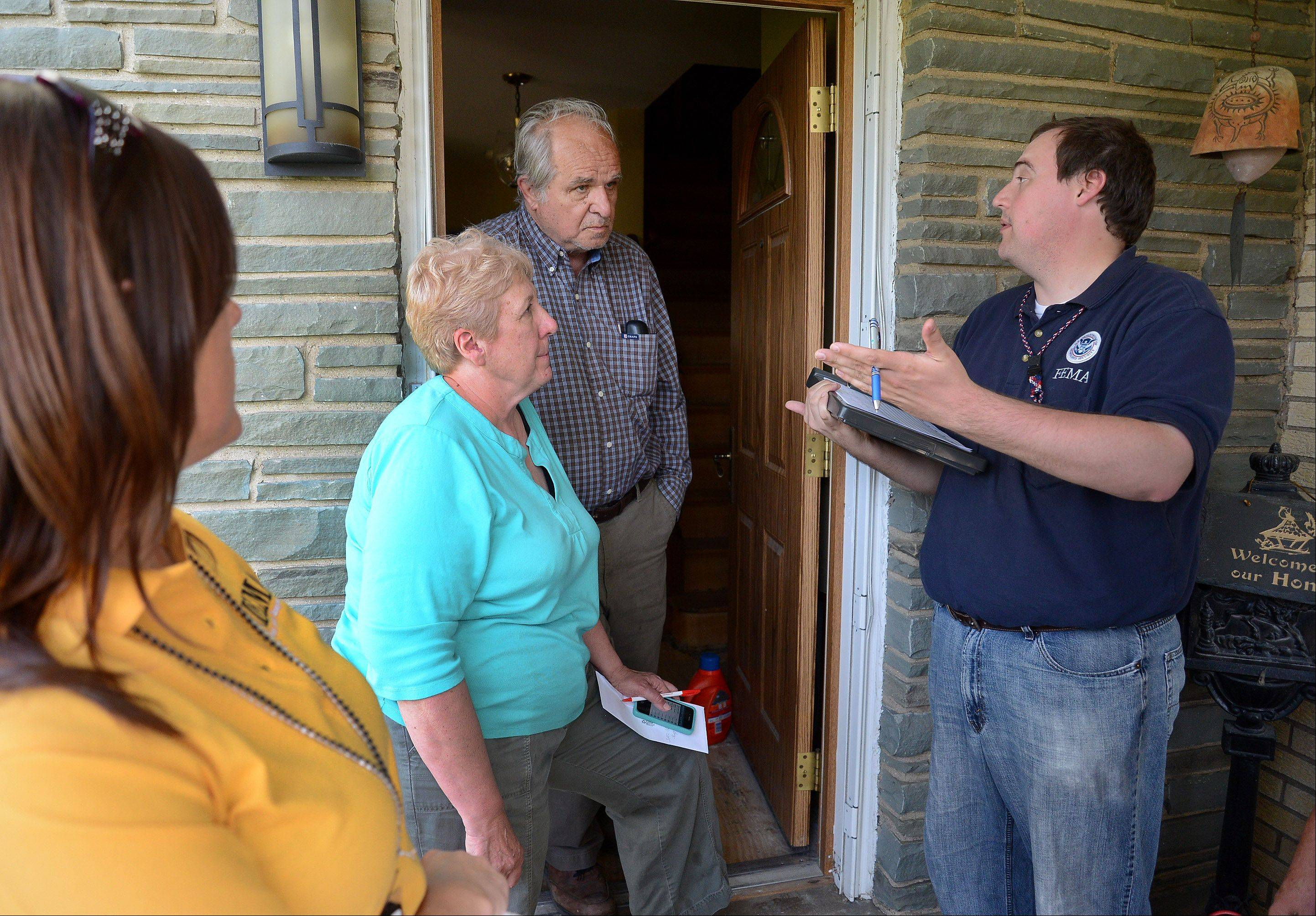 FEMA assessment specialist Seth Gardner, right, talks with Des Plaines homeowners Stan Lubash and Cynthia Mitchell to assess flood damage.