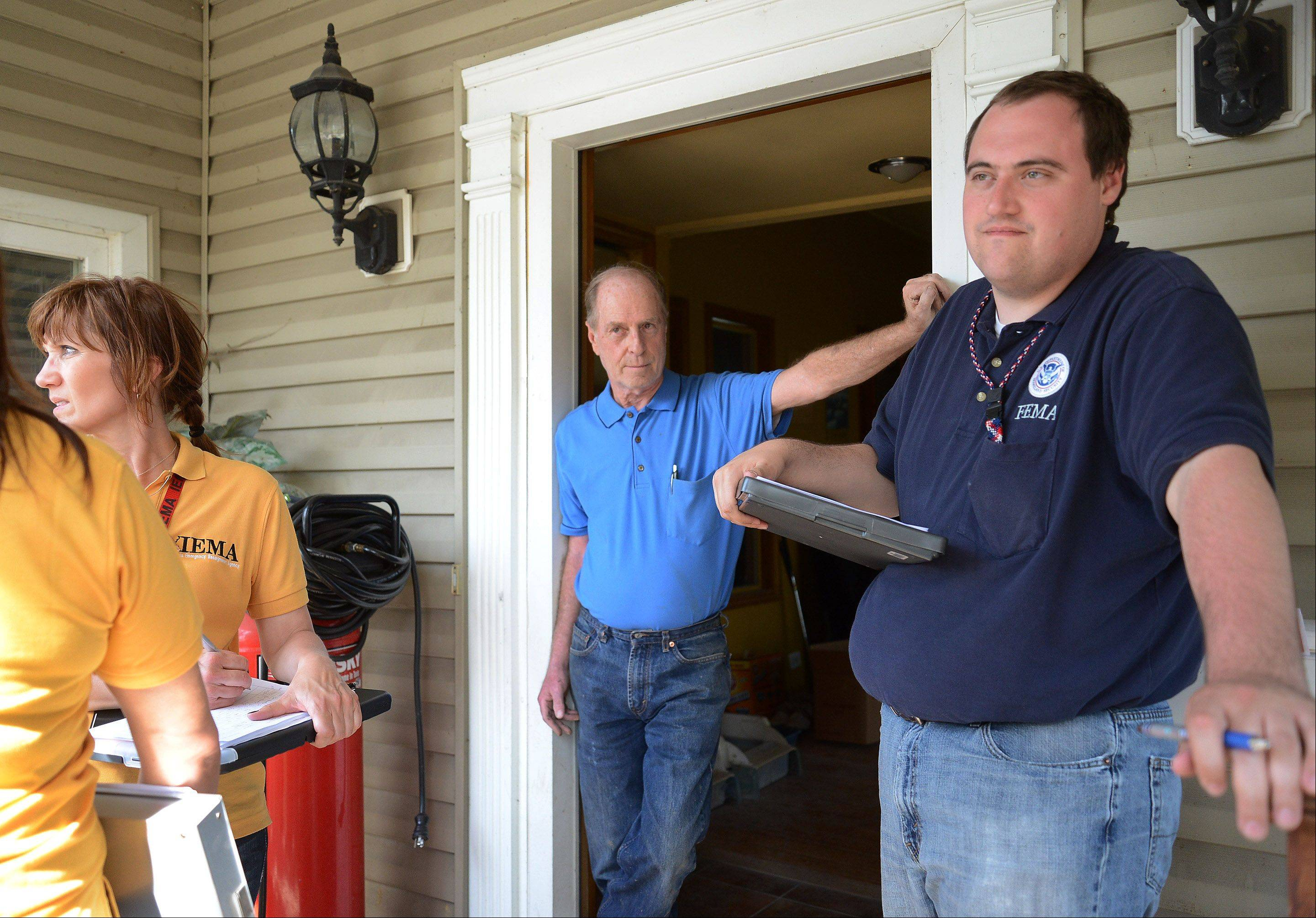 FEMA assessment specialist Seth Gardner, right, talks with Des Plaines homeowner Tom Hooper about his flood damage. Hooper's house is one of two along Big Bend Drive that were the first hit during a flood.