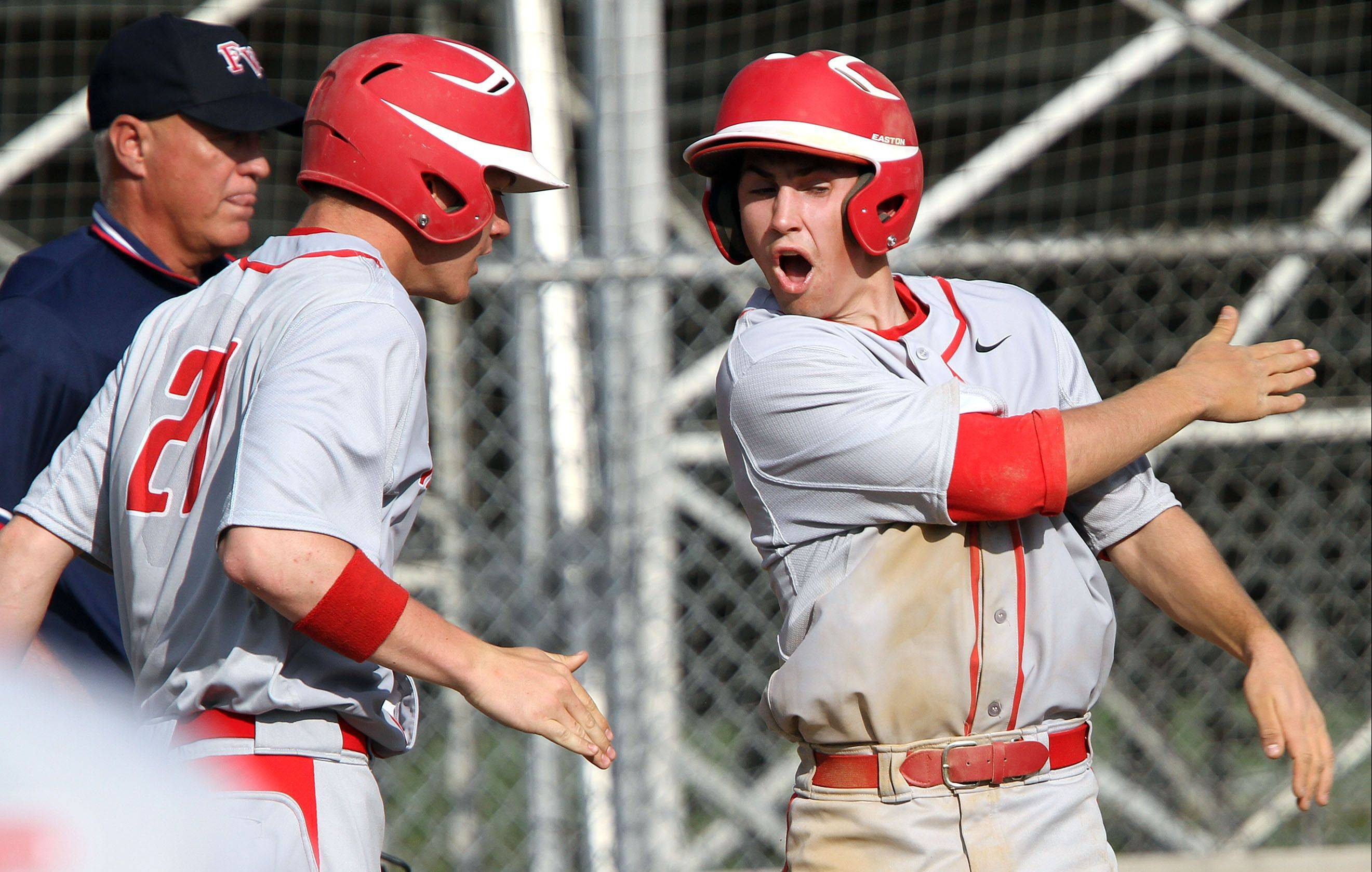 Mundelein's Zach Osisek , right, high-fives teammate Luke Adams after Osisek scored after a play at the plate at Libertyville on Wednesday.
