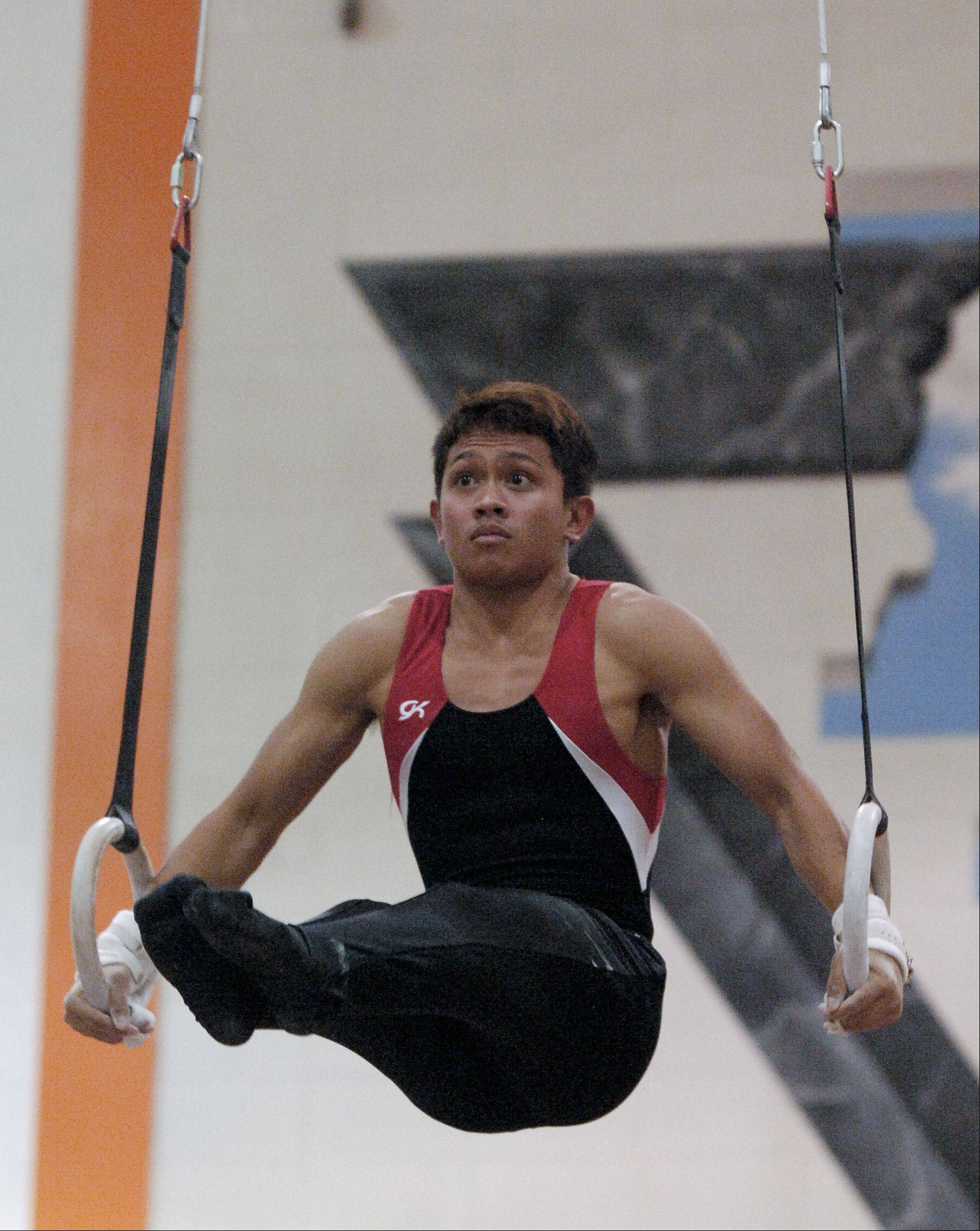 Melik Prum of Glenbard East performs on the Still Rings during the Wheaton Warrenville South boys gymnastics sectional, Wednesday.