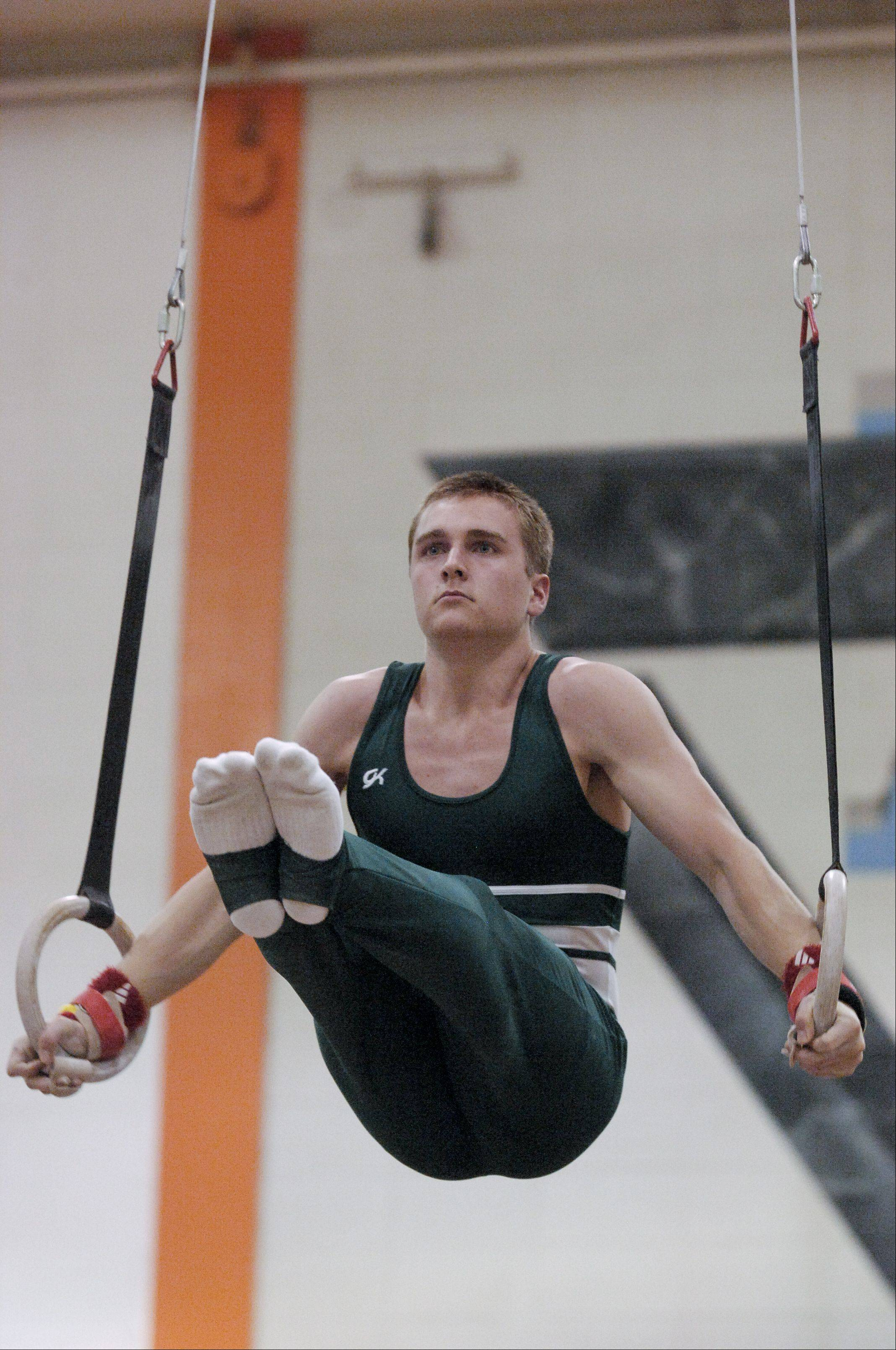 Charlie Kummerere of Glenbard West performs on the Still Rings during the Wheaton Warrenville South boys gymnastics sectional, Wednesday.