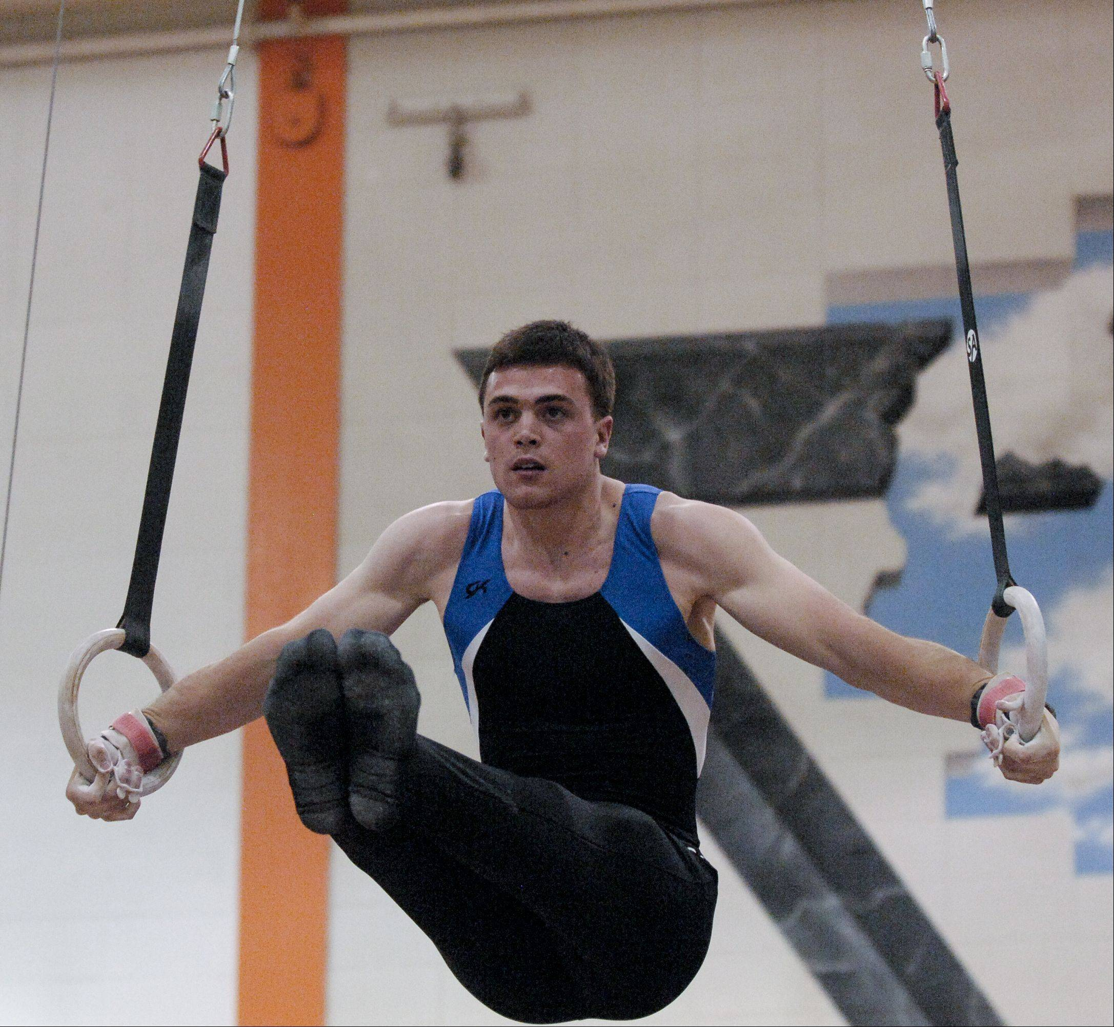 Evan Murray of Wheaton Coop performs on the Still Rings during the Wheaton Warrenville South boys gymnastics sectional, Wednesday.