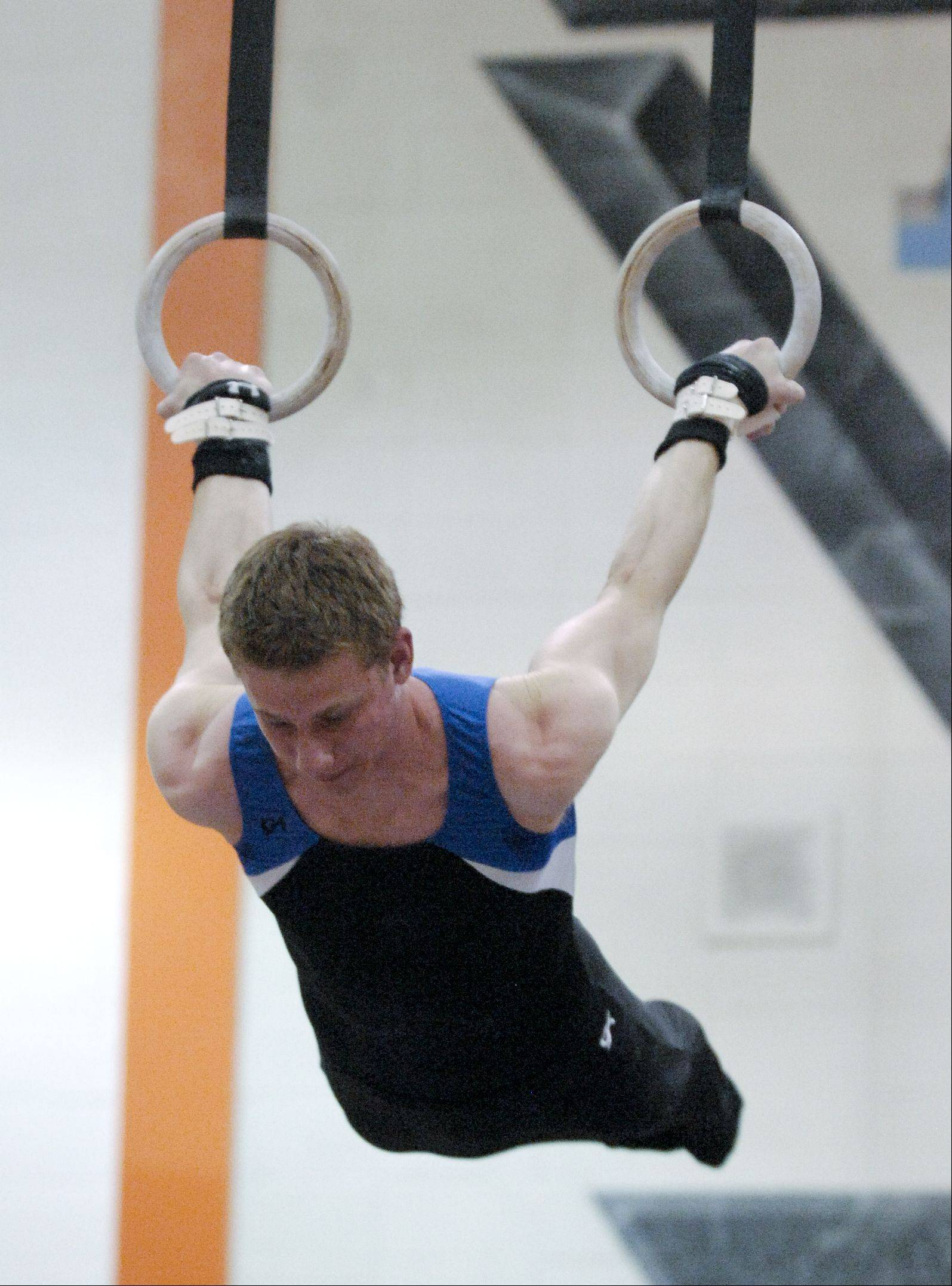 Danny Heller of Wheaton Coop performs on the Still Rings during the Wheaton Warrenville South boys gymnastics sectional, Wednesday.