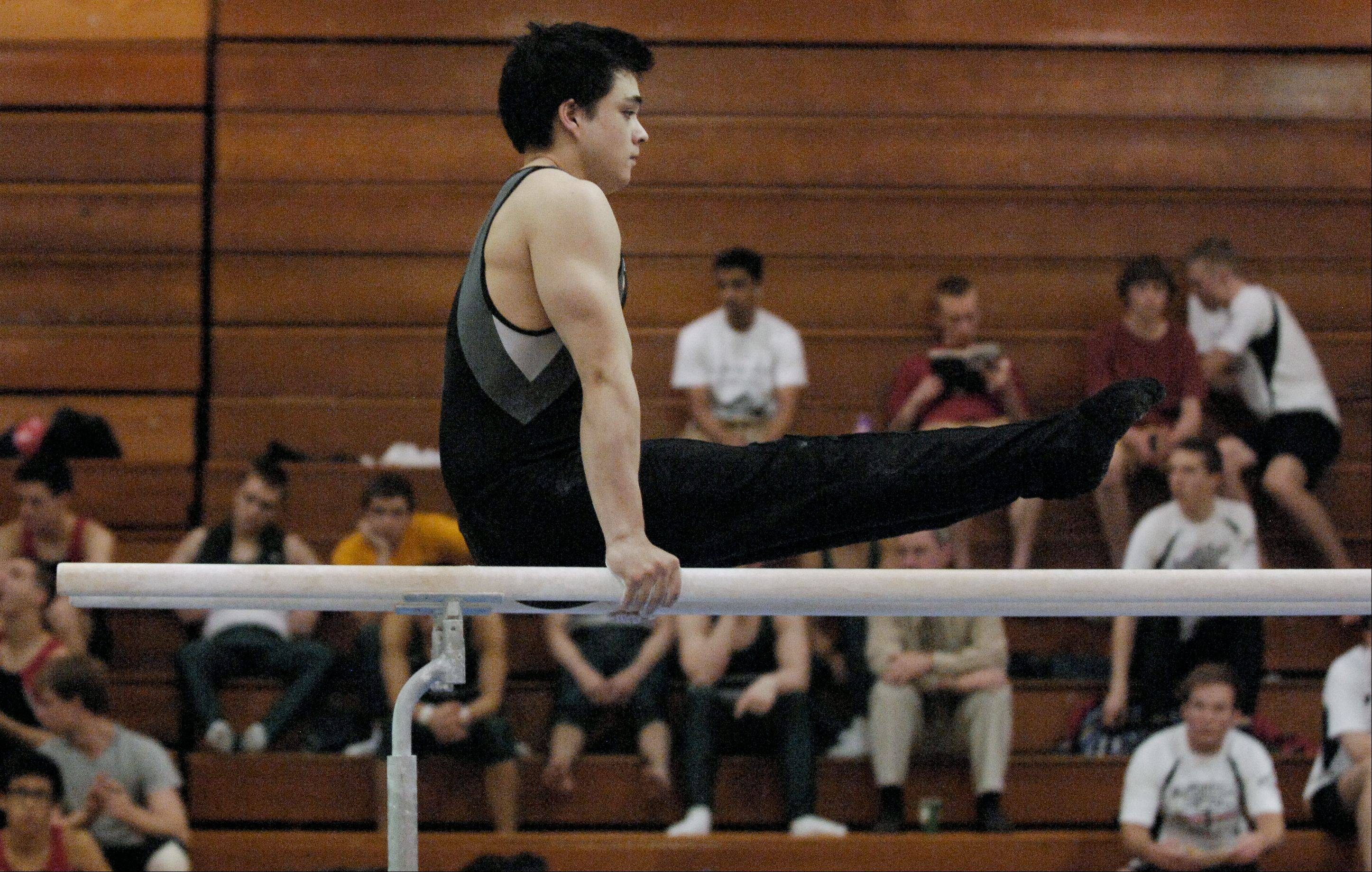 Keawe Winstead of Willowbrook performs on the Parallel Bars during the Wheaton Warrenville South boys gymnastics sectional, Wednesday.