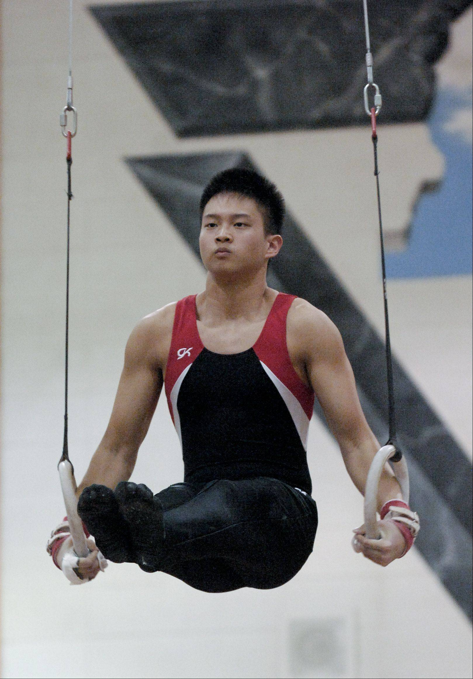 Duyan Nguyen of Glenbard East performs on the Still Rings during the Wheaton Warrenville South boys gymnastics sectional, Wednesday.