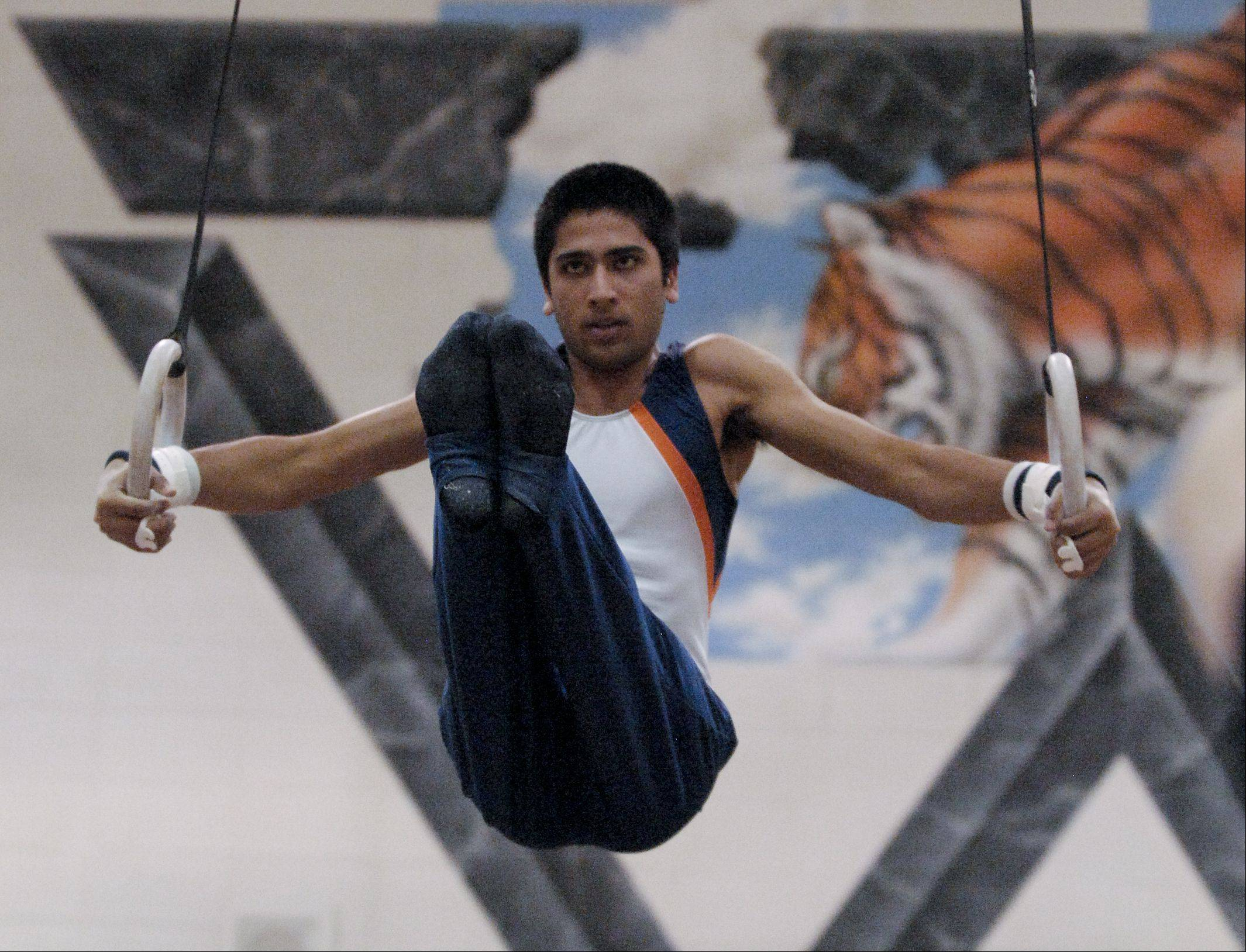 Akshay Harisparad of Naperville North performs on the Still Rings during the Wheaton Warrenville South boys gymnastics sectional, Wednesday.