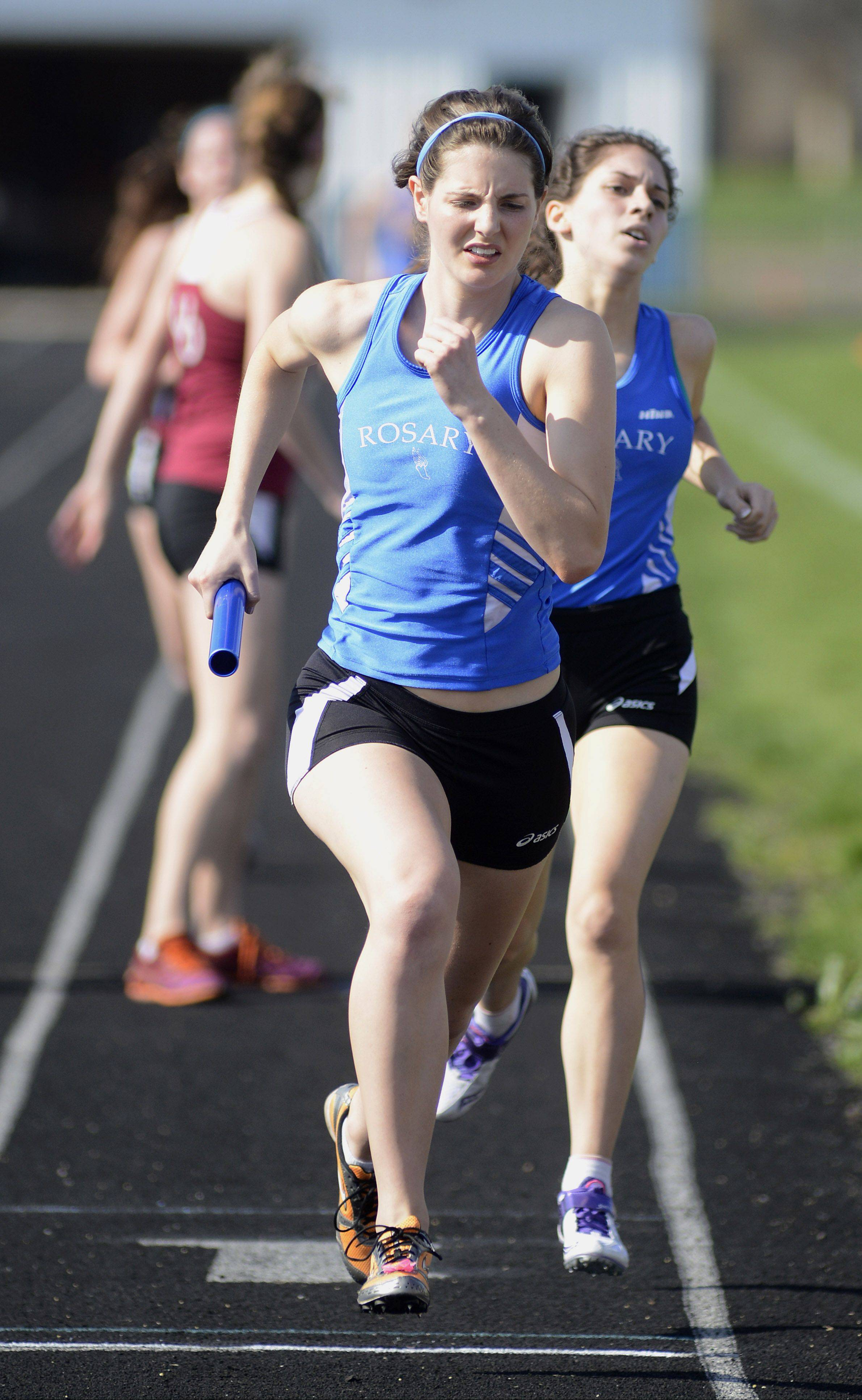 Rosary's Amelia Anderson takes the baton from Courtney Cox at the Suburban Christian Conference meet Wednesday.