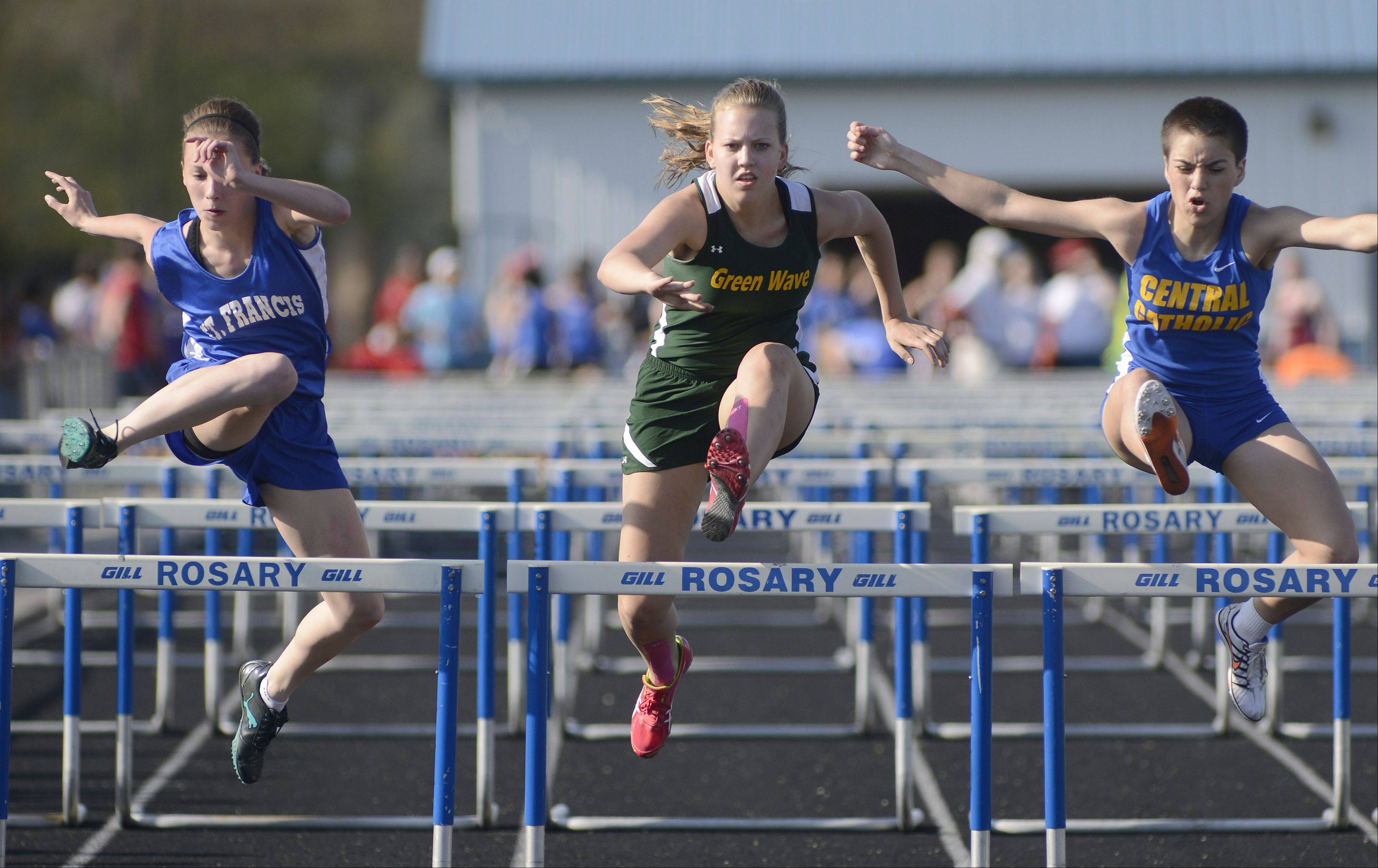 St. Francis' Kate Howard, St. Edward's Clare Cholwea and Aurora Central Catholic's Cynthya Elizondo in the first heat of the 100 meter hurdles at the Suburban Christian Conference on Wednesday, May 1.