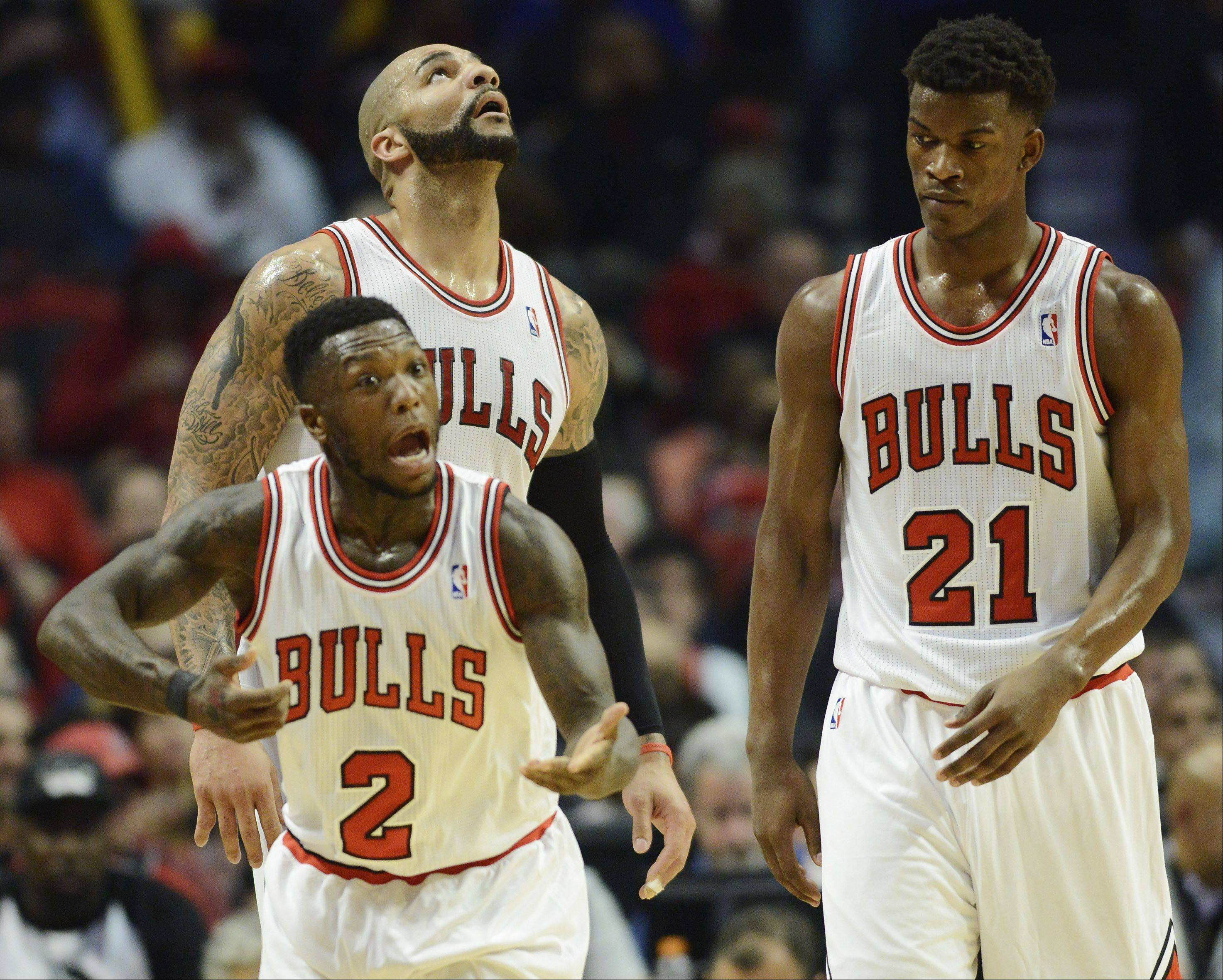 Nate Robinson of the Chicago Bulls, front, reacts after drawing contact on his chin from a Brooklyn Nets player in Game 6 of the first round playoff game at the United Center in Chicago, Thursday, May 2, 2013. With him are teammates Carlos Boozer, left, and Jimmy Butler.