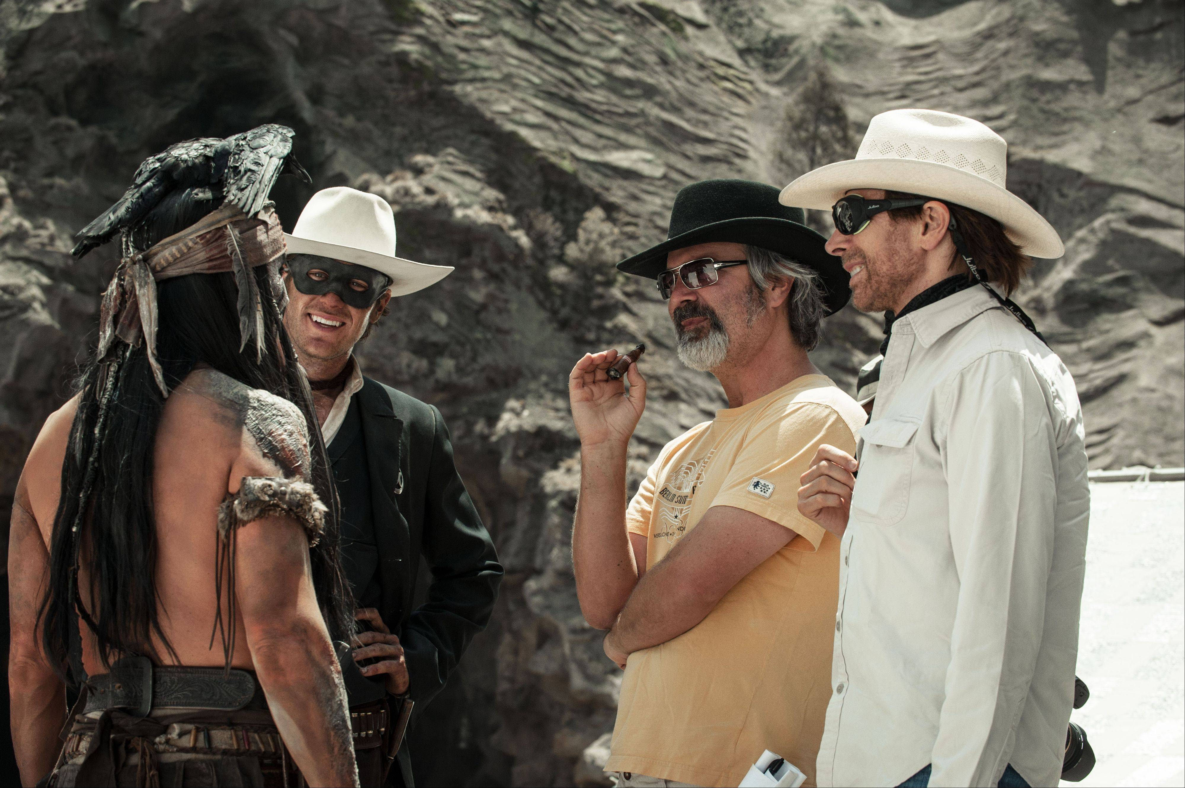 "Johnny Depp as Tonto, Armie Hammer as the Lone Ranger, director, Gore Verbinski and producer, Jerry Bruckheimer, on the set of ""The Lone Ranger."""