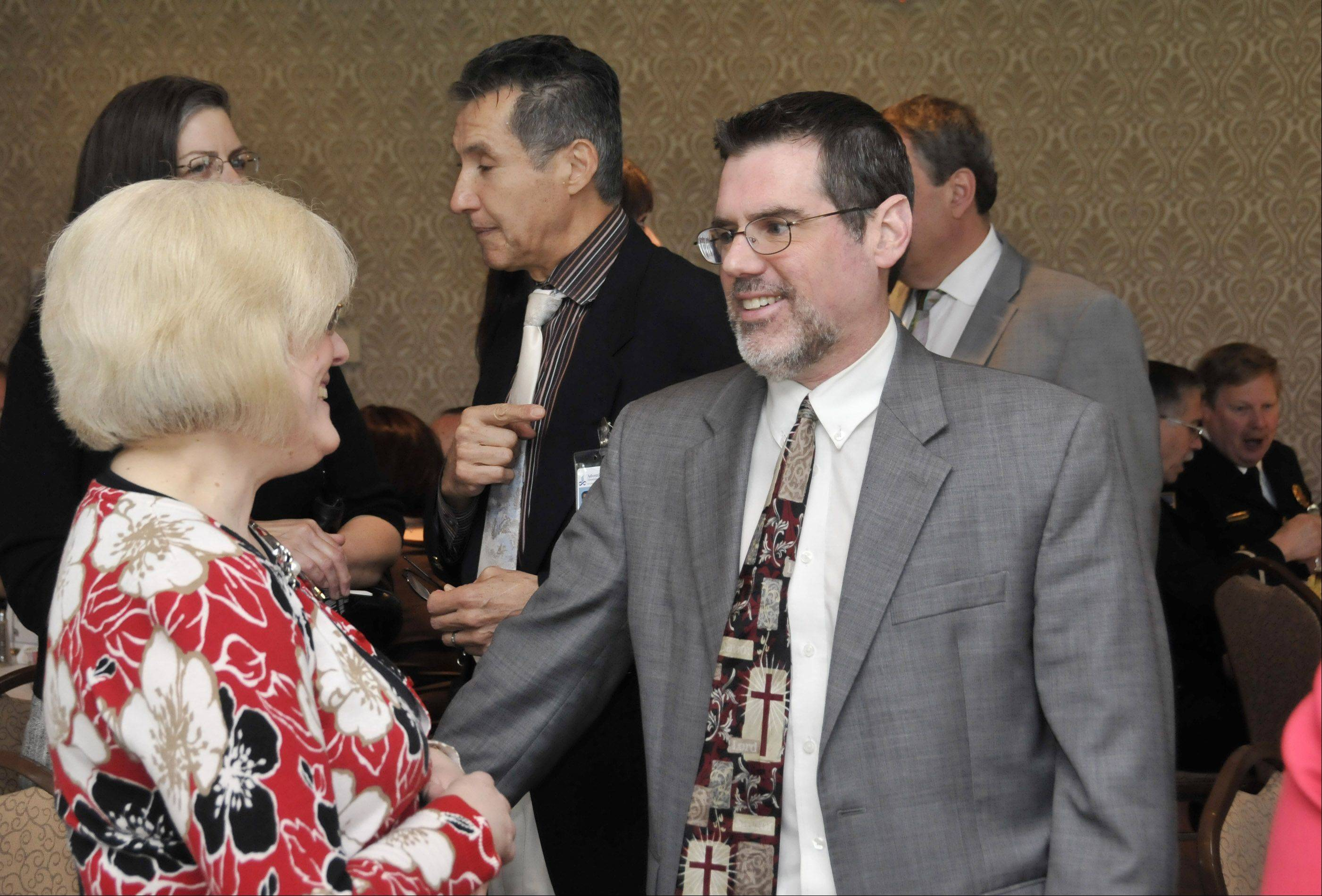 Featured speaker, Rev. David Sitler from the Glen Ellyn Seventh-day Adventist Church, chats with hospital chaplain Debra Hill, left, at Thursday's National Day of Prayer breakfast in Glendale Heights.