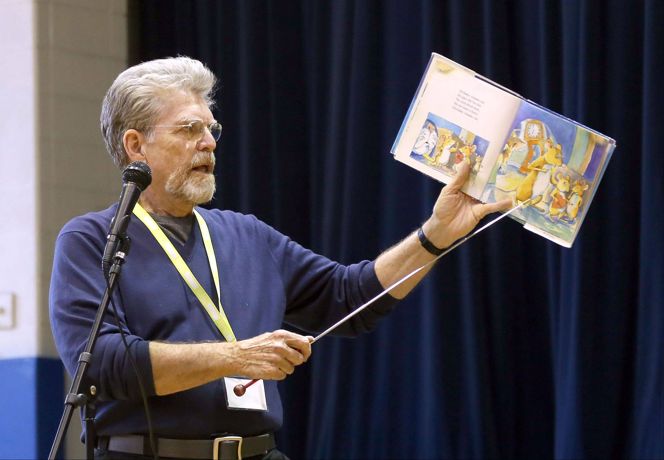 Author and former first grade teacher Jim Aylesworth reads one of the 34 books he has written to students at May Whitney Elementary School in Lake Zurich on Thursday.