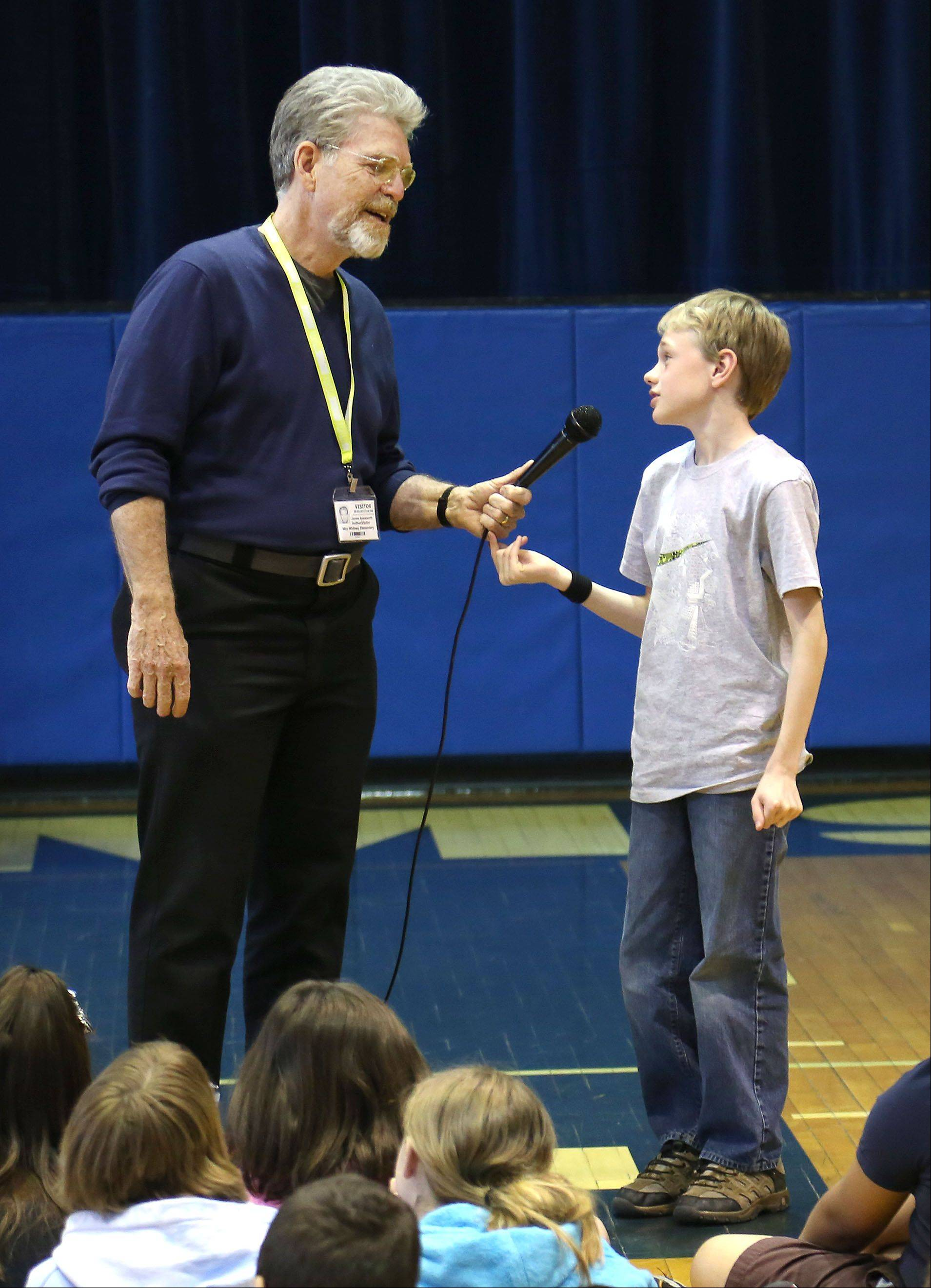 Author Jim Aylesworth talks with fifth-grader Jack Murray during an assembly at May Whitney Elementary School in Lake Zurich Thursday. Aylesworth has written 34 picture books for children.