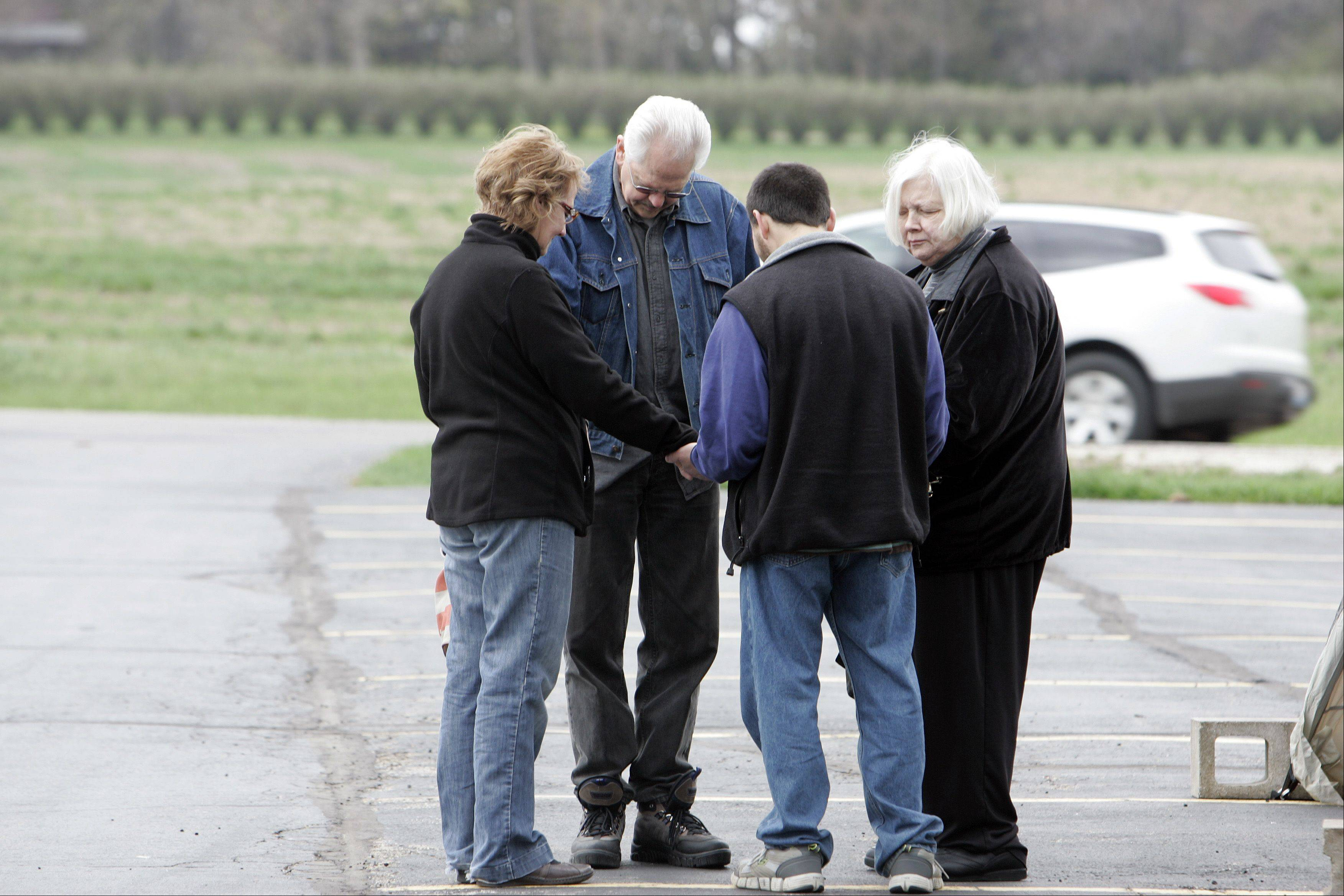 "Lynette Ohse of St. Charles, from left, Don Gorder of Huntley, George Delask of DeKalb and Char Sportsman of St. Charles share a prayer Thursday at Country Evangelical Covenant Church in Campton Hills. The church hosted a ""Drive-Through"" prayer service in its parking lot at McDonald Road and Route 47 on the National Day of Prayer."