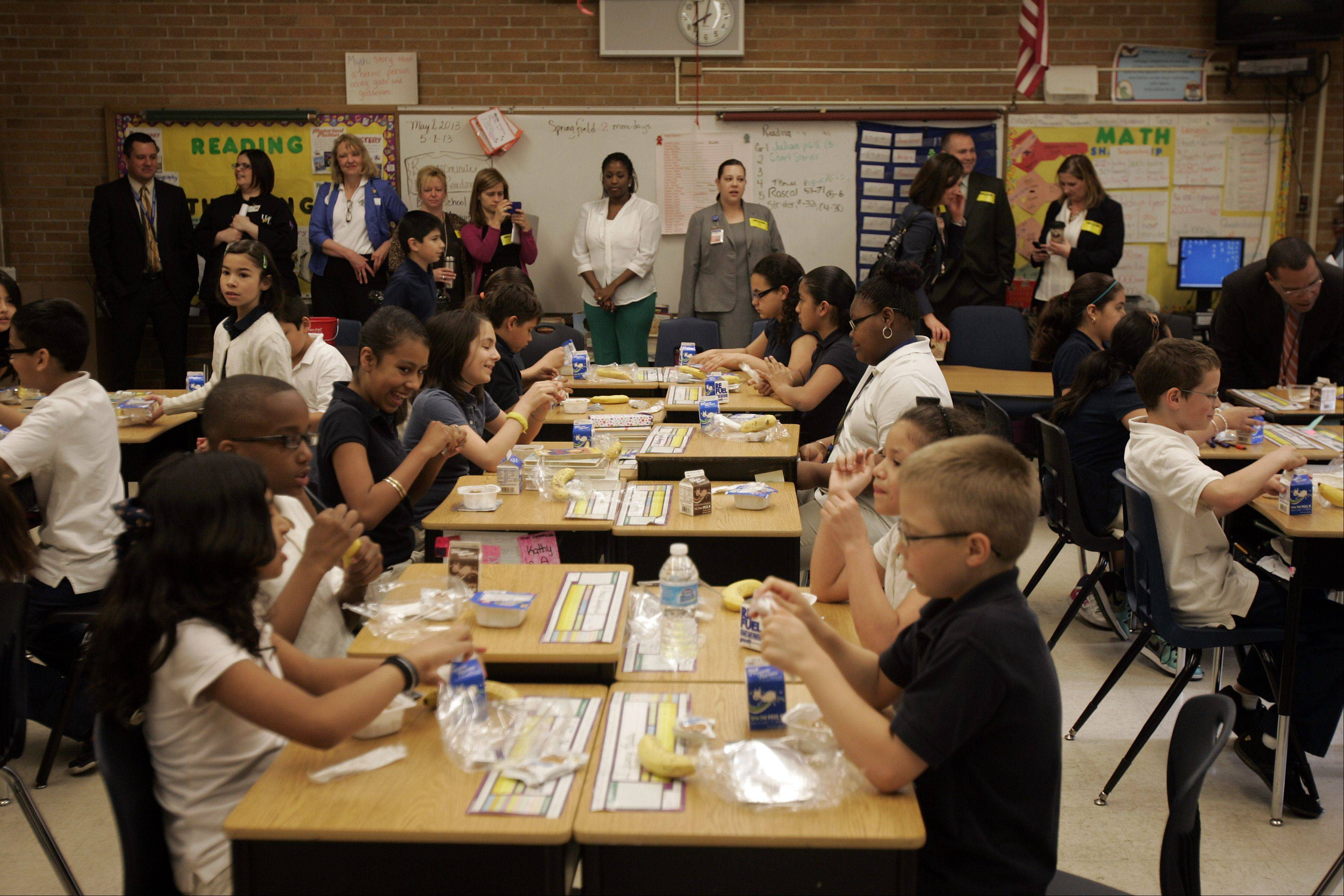 Observers get a firsthand look as students at Harriet Gifford Elementary School in Elgin enjoy breakfast Thursday as part of the Breakfast in the Classroom program.
