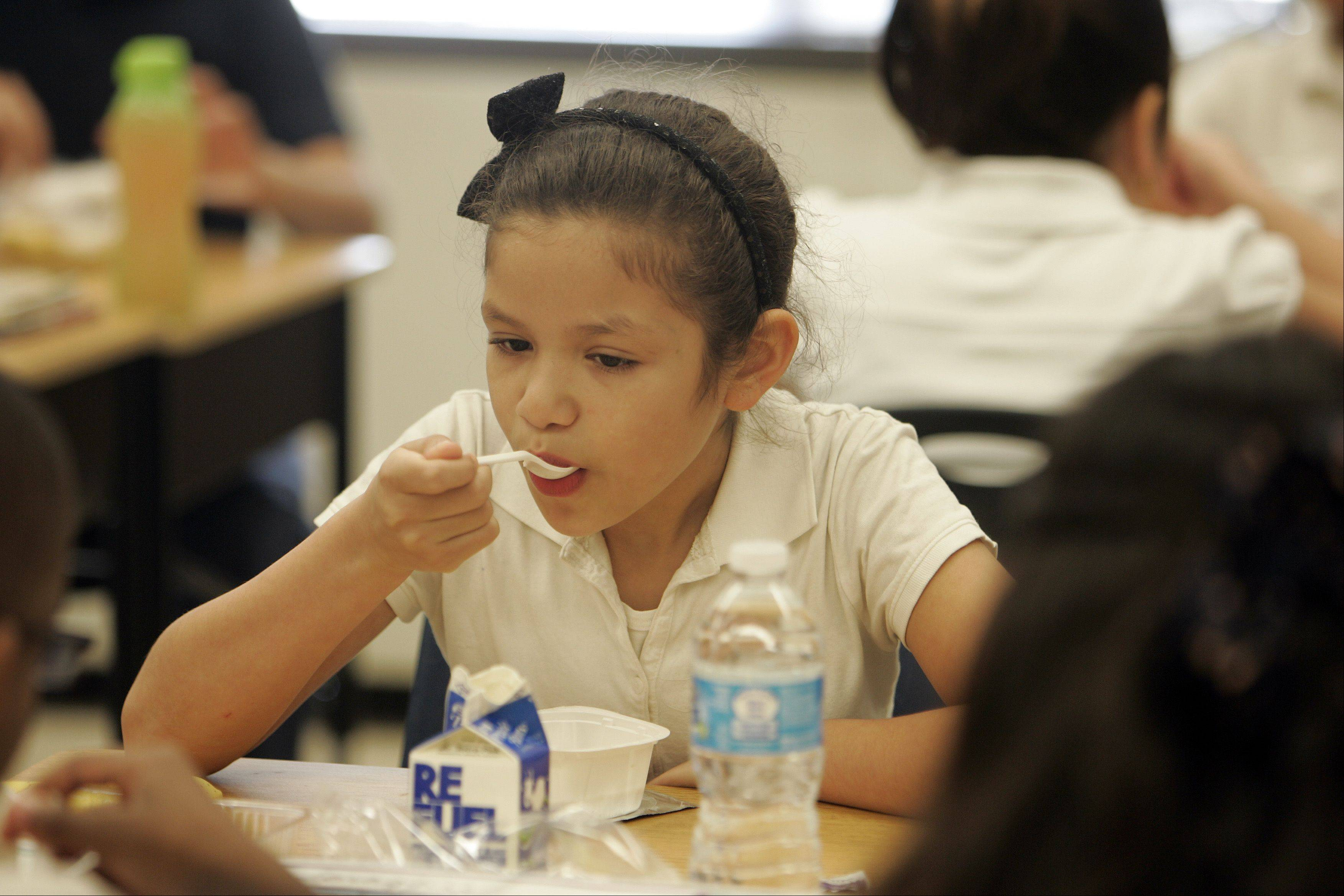 Delilah Herrera, 10, a fourth-grade student at Harriet Gifford Elementary School in Elgin, enjoys breakfast Thursday morning.