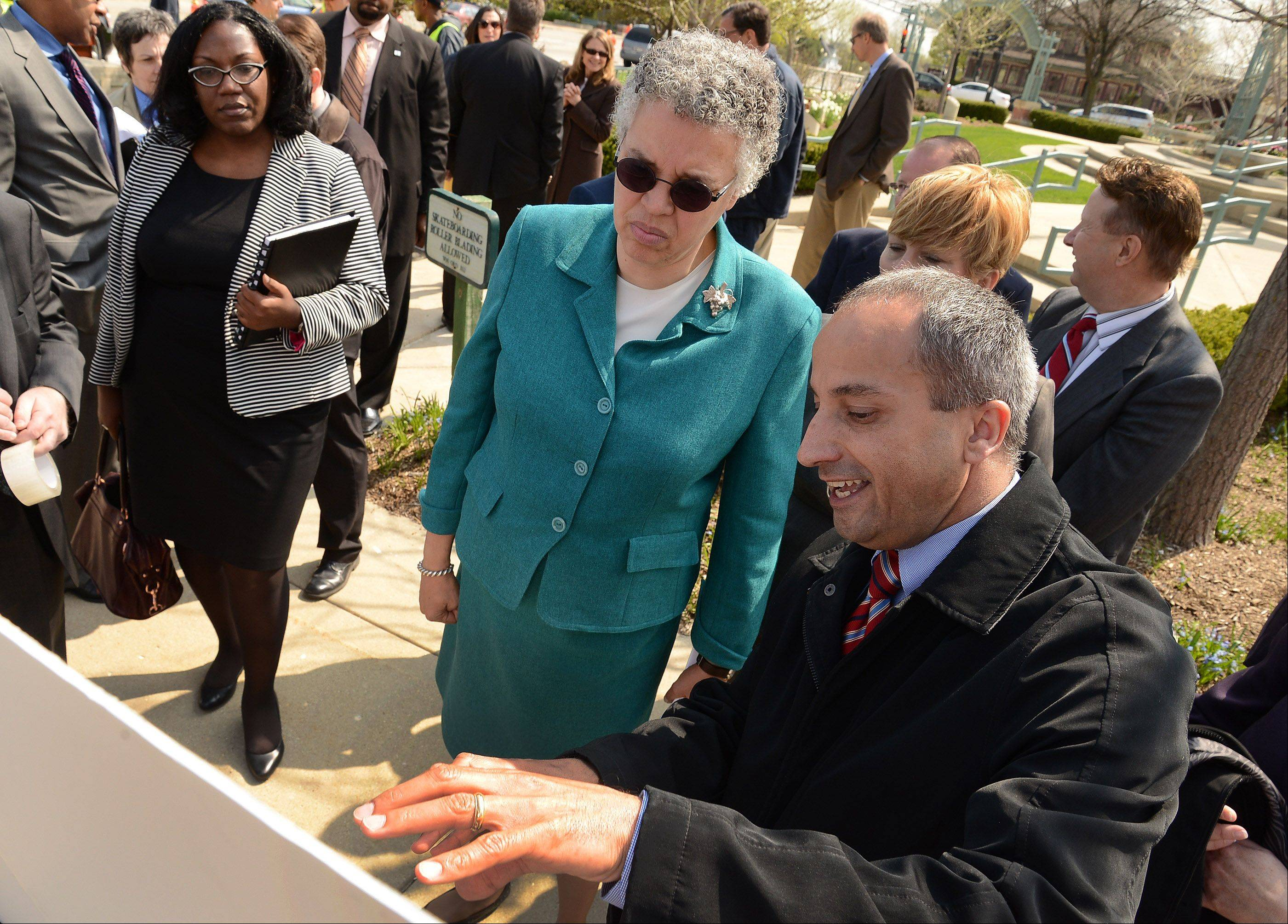 John Yonan, superintendent of the Cook County Transportation and Highway Department, points out several projects in the works to Cook County Board President Toni Preckwinkle during a news conference at the corner of Roselle and Schaumburg Roads in Schaumburg Thursday morning.