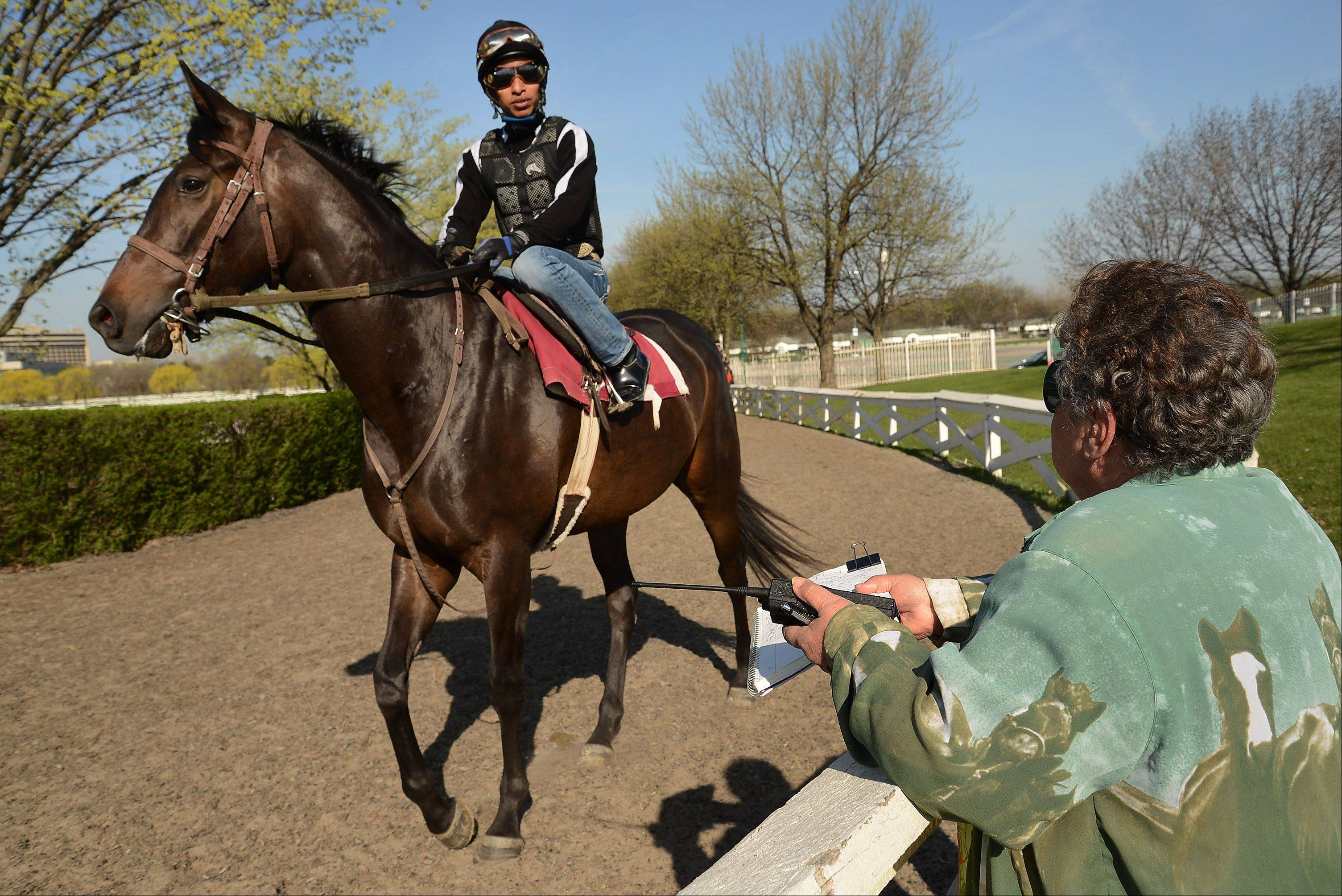 Spotter Gina Pantano checks in a horse on its way to the track in preparation for opening day at Arlington International Racecourse. Some well-known trainers and jockeys will call Arlington home this summer.