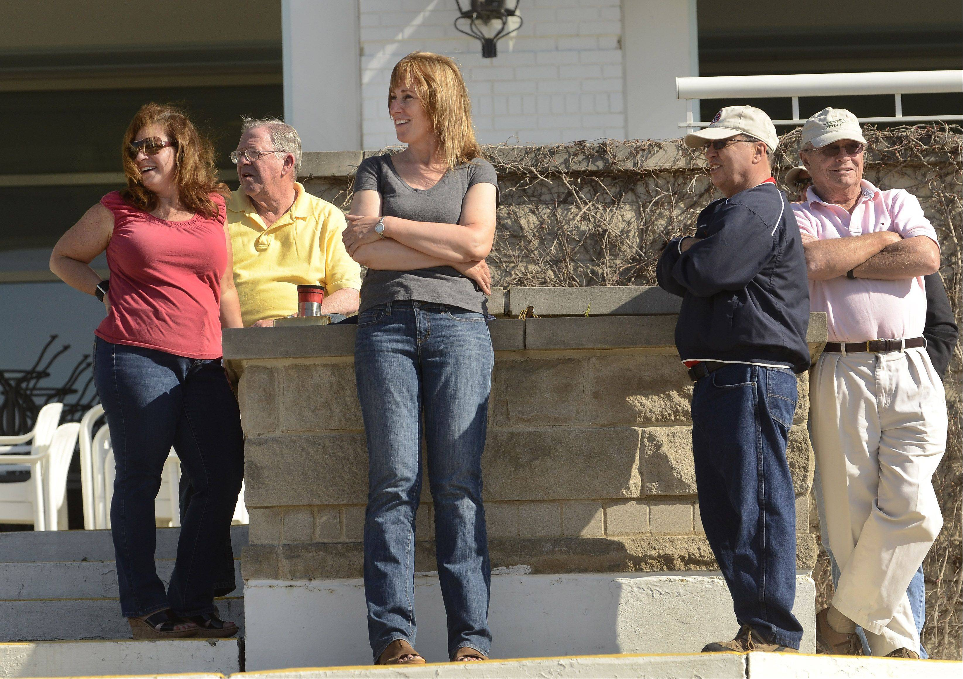 Horse owner Theresa Nugent, of Chicago, center, and Michael Campbell, President of the Illinois Thoroughbred Horseman's Association, to Nugent's left, watch with other owners as horses work out in preparation for opening day at Arlington International Racecourse.