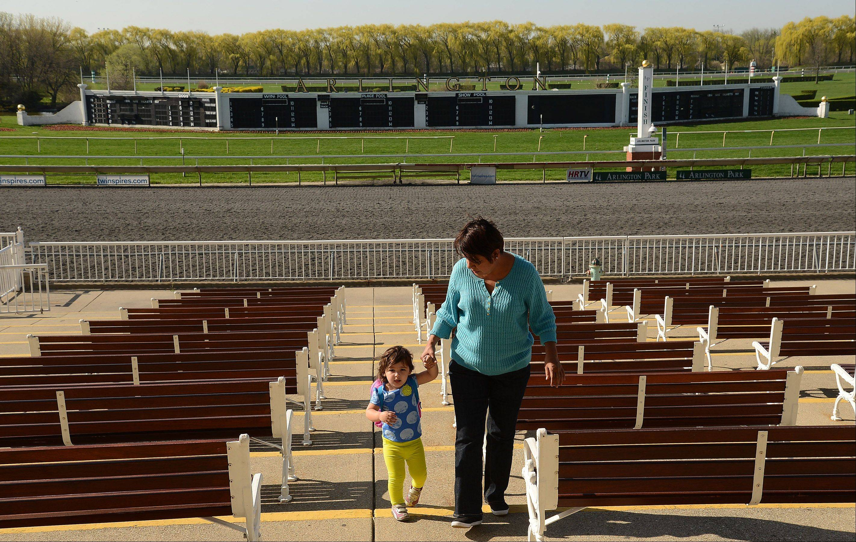 Aide Silva, wife of trainer Carlos Silva, walks with her granddaughter through the grandstand watching horses work out in preparation for opening day at Arlington International Racecourse.