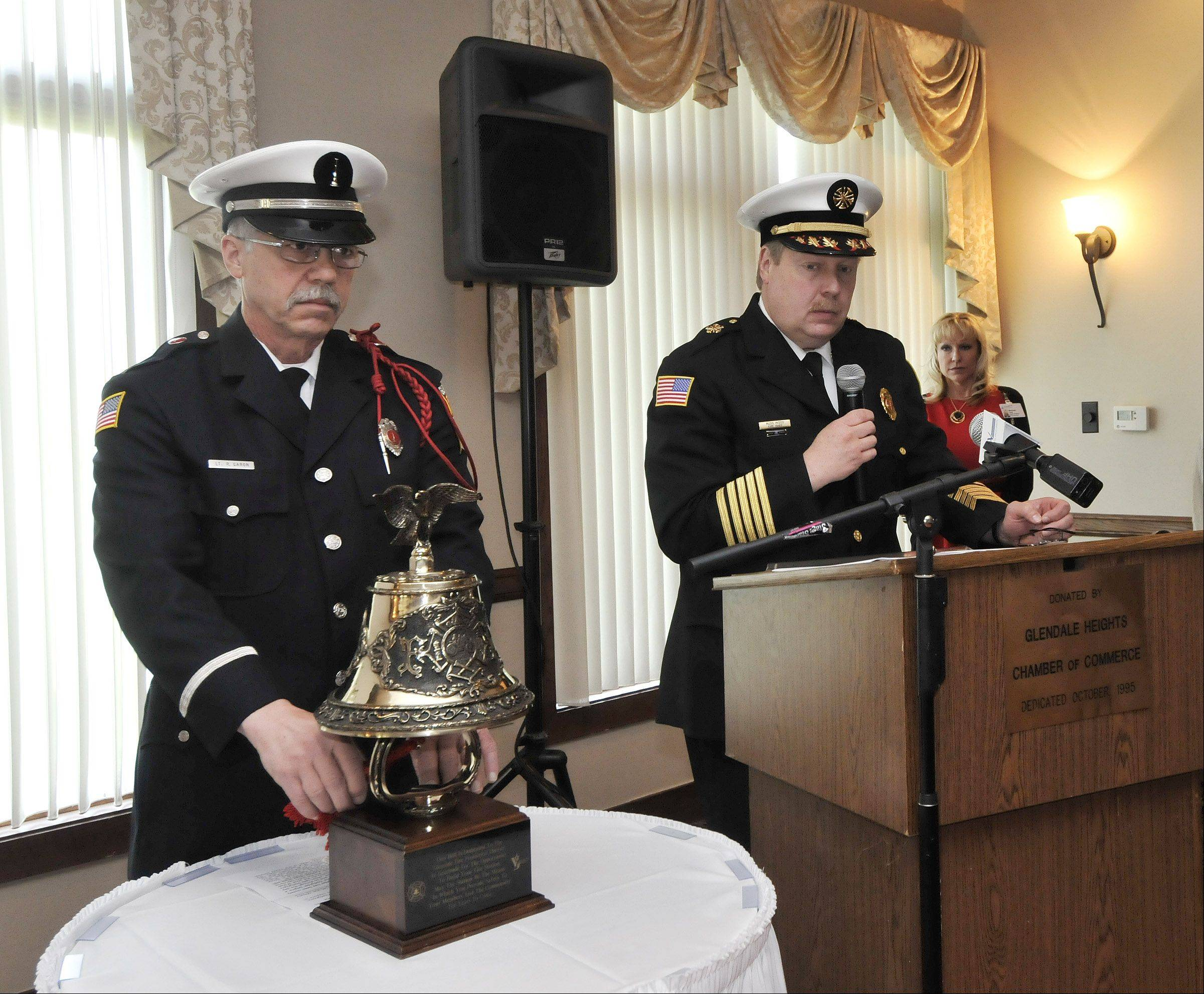 To honor fallen firefighters and other first responders, Glenside Fire Department Lt. Bob Garon, left, rings a memorial bell, while Chief Russ Wood reads a list of those honored.