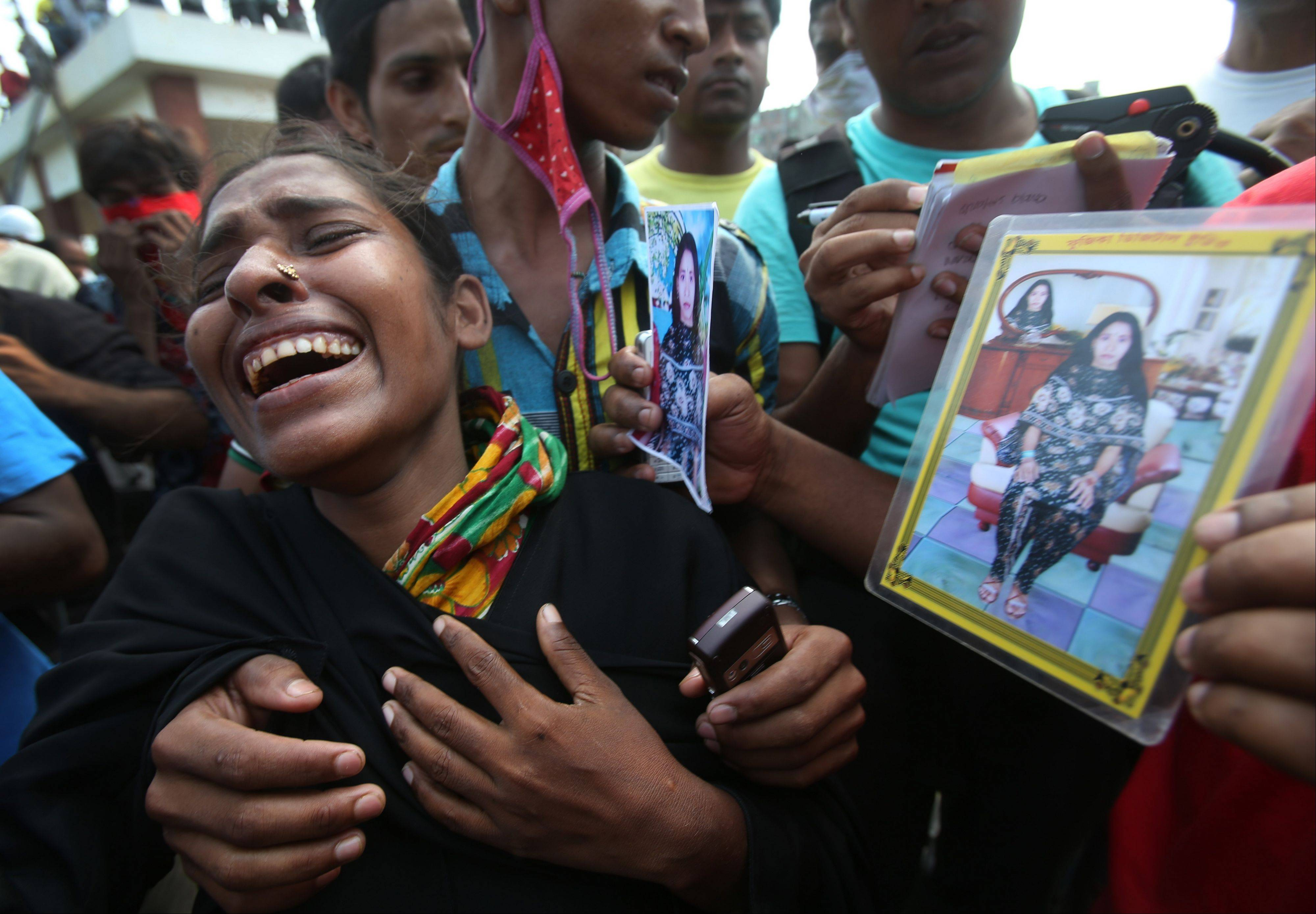 Farida, center, cries as she searches for her sister-in-law Fahima, seen in photographs. Just moments before Fahima was to be placed in one of the dozens of unmarked graves dug for victims of Bangladesh's building collapse, Farida was able to claim and leave with her sister-in-law's body.