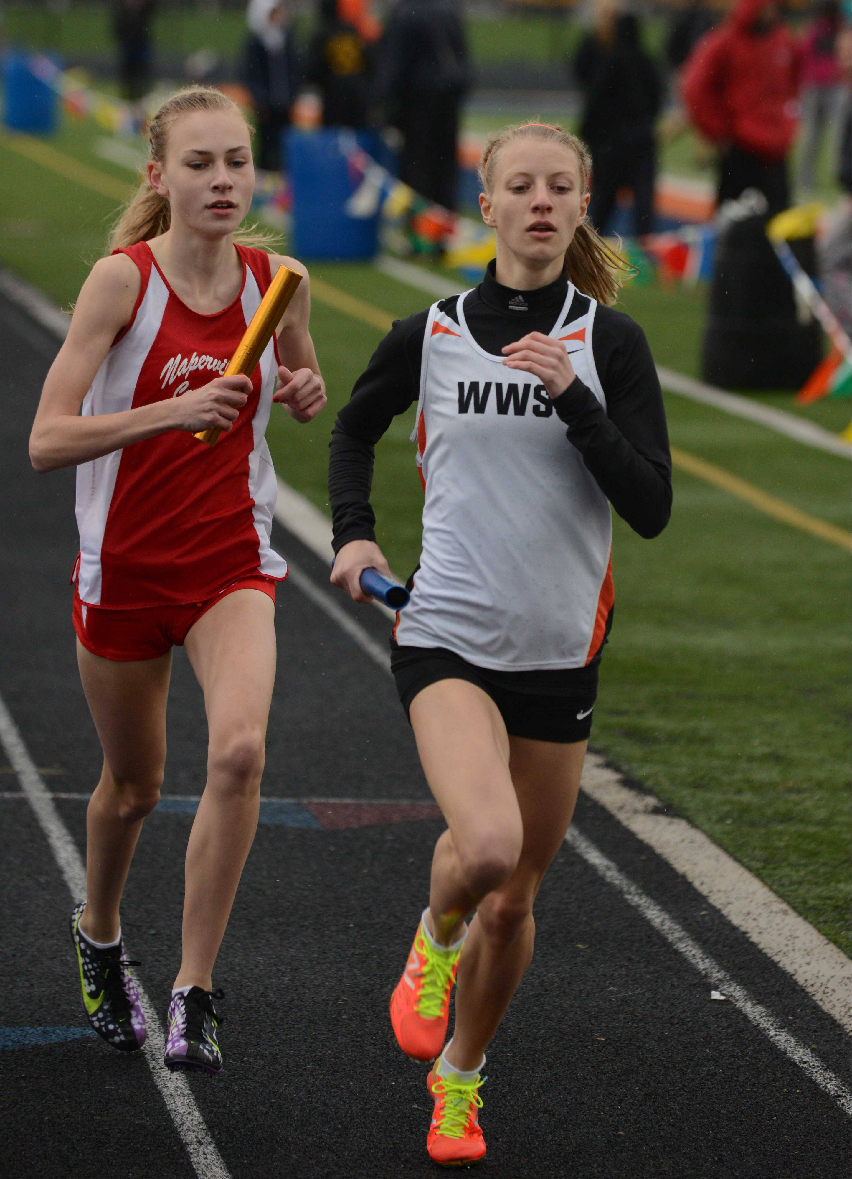 Rachel Hoffman, left of Napeville Central and Helen Majer of Wheaton Warrenville South run the 4x800 during the DuPage Valley Conference girls track finals Thursday.