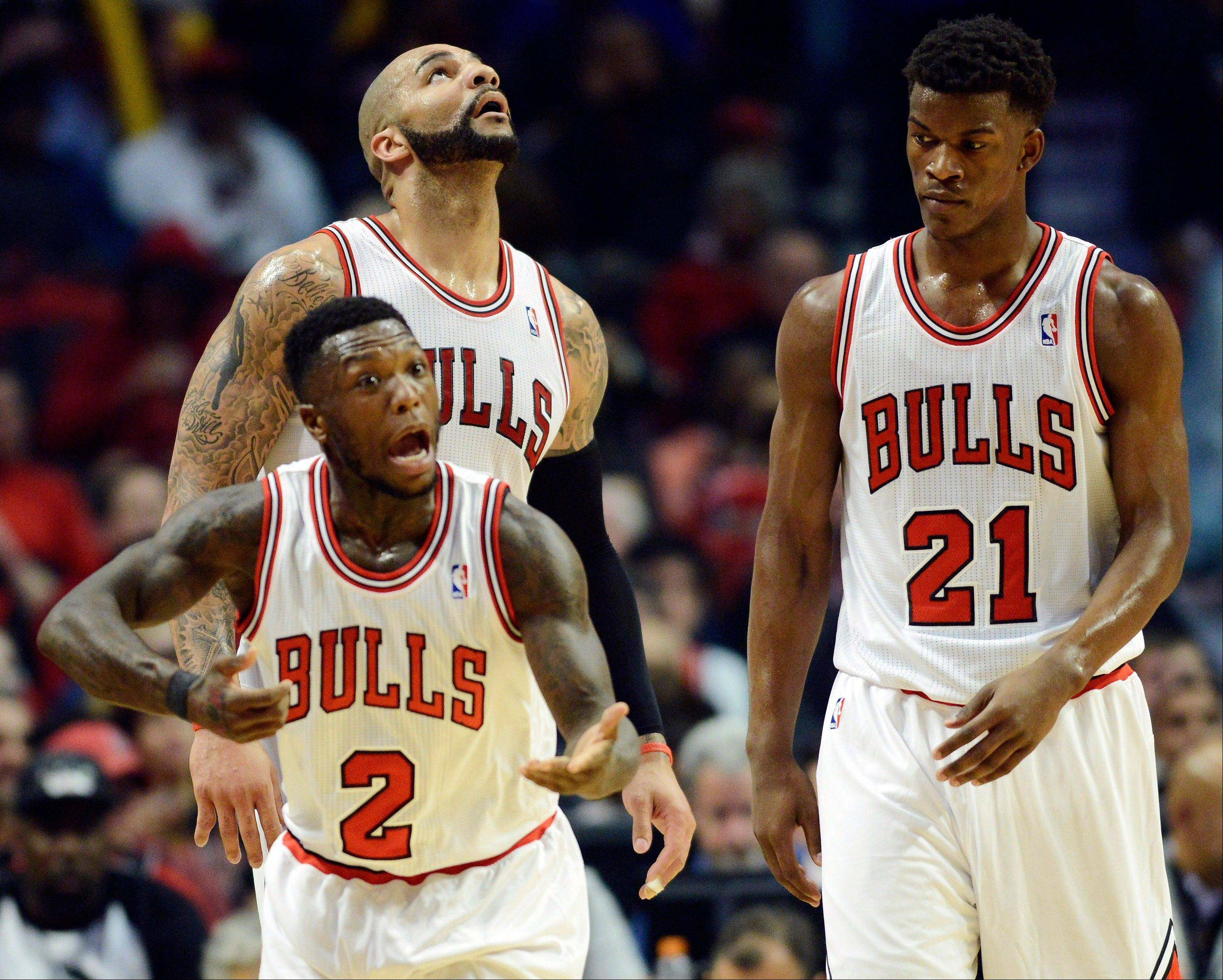 The Bulls' Nate Robinson (2) reacts after drawing contact from a Brooklyn Nets player as Carlos Boozer, rear left, and Jimmy Butler look on during Game 6 of their first-round NBA basketball playoff series at the United Center. The Nets won 95-92.