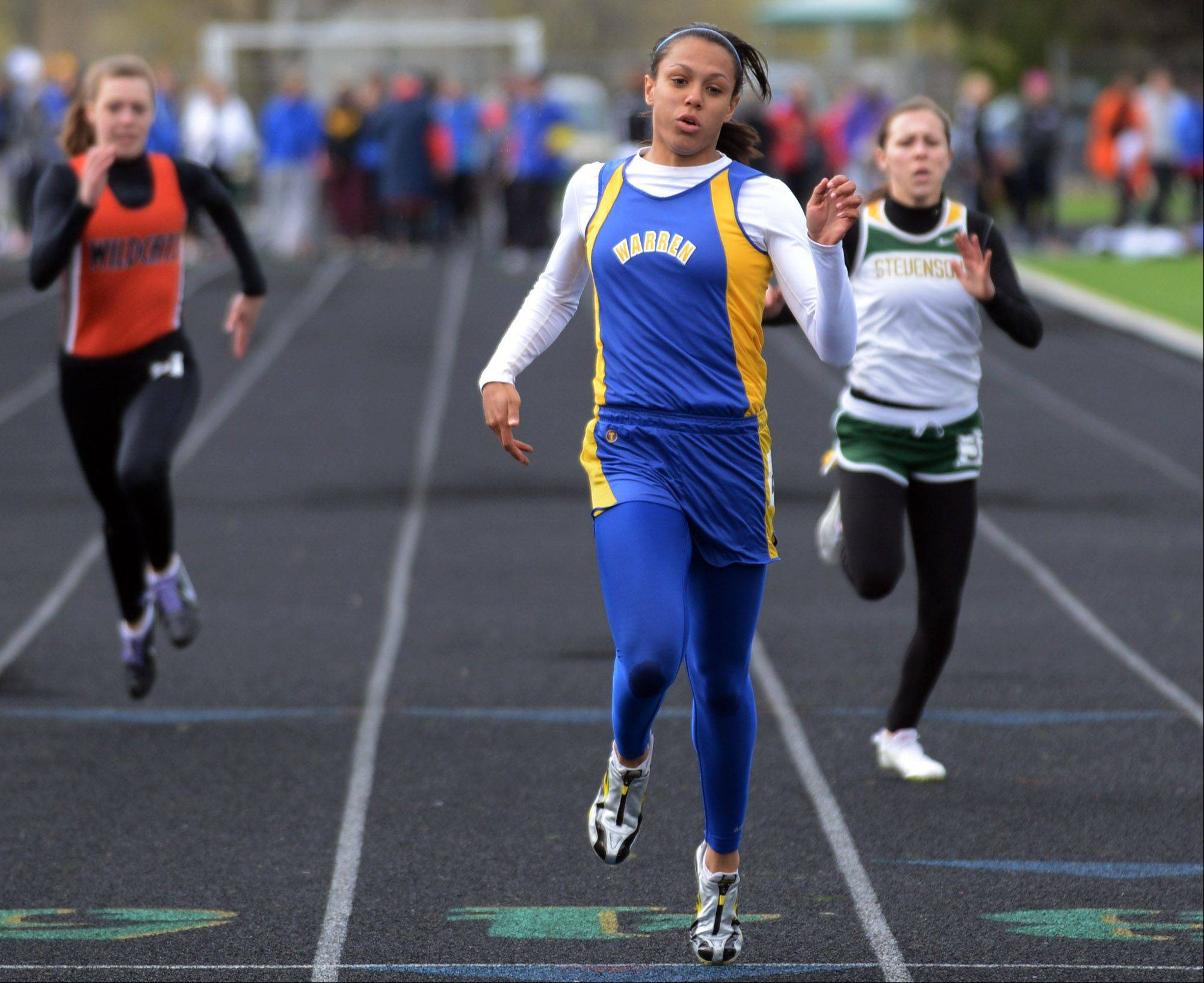 Warren's Brittny Ellis, center, crosses the finish line in a 100-meter dash preliminary race ahead of Libertyville's Megan Henderson, left, and Stevenson's Lily Marks Thursday at the North Suburban Conference girls track meet in Lincolnshire.