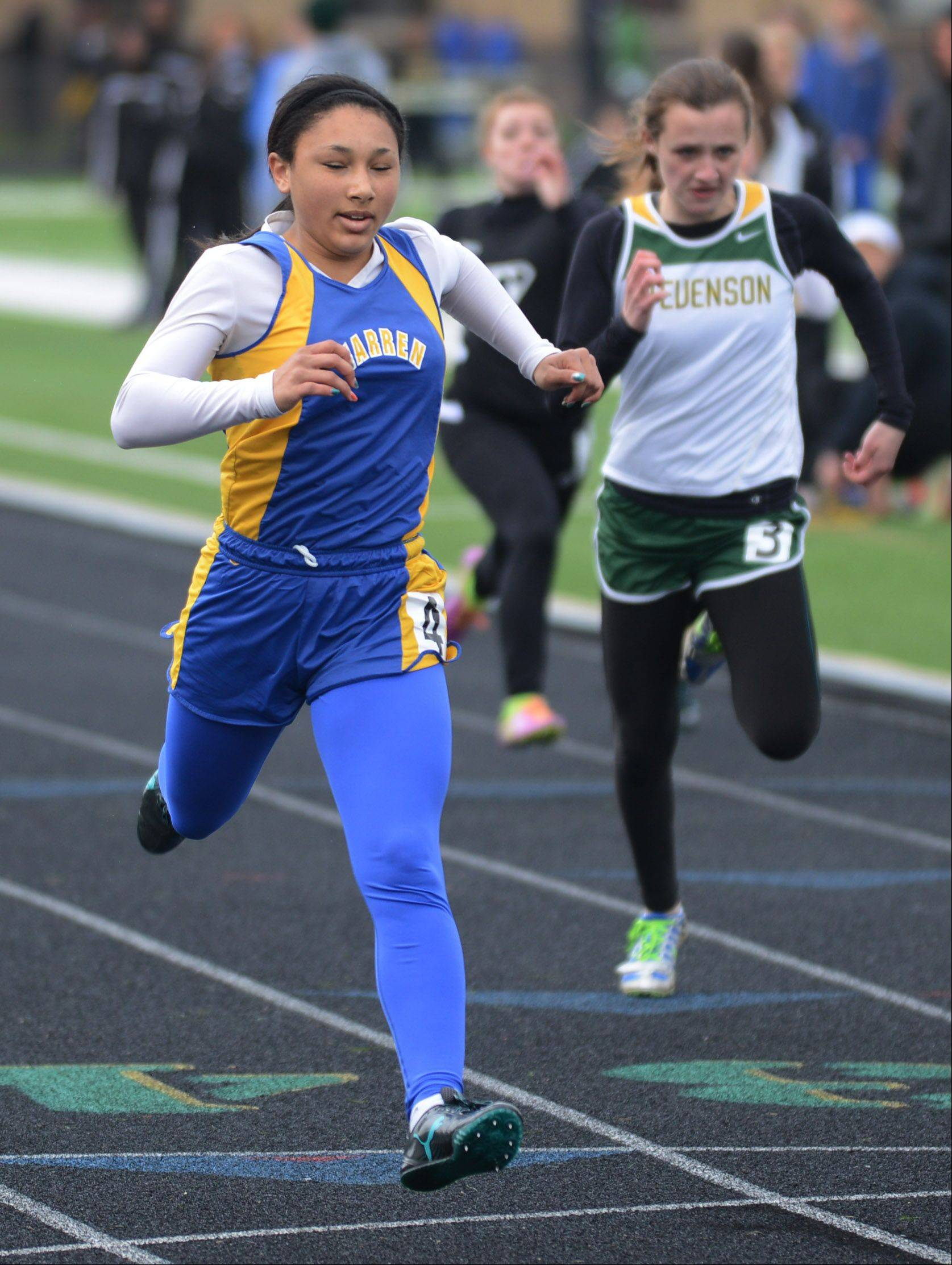 Warren's Autumn Santos, left, comes in first ahead of Stevenson's Charlotte Langbo in a 100-meter dash prelim race at Thursday's North Suburban Conference girls track meet in Lincolnshire.