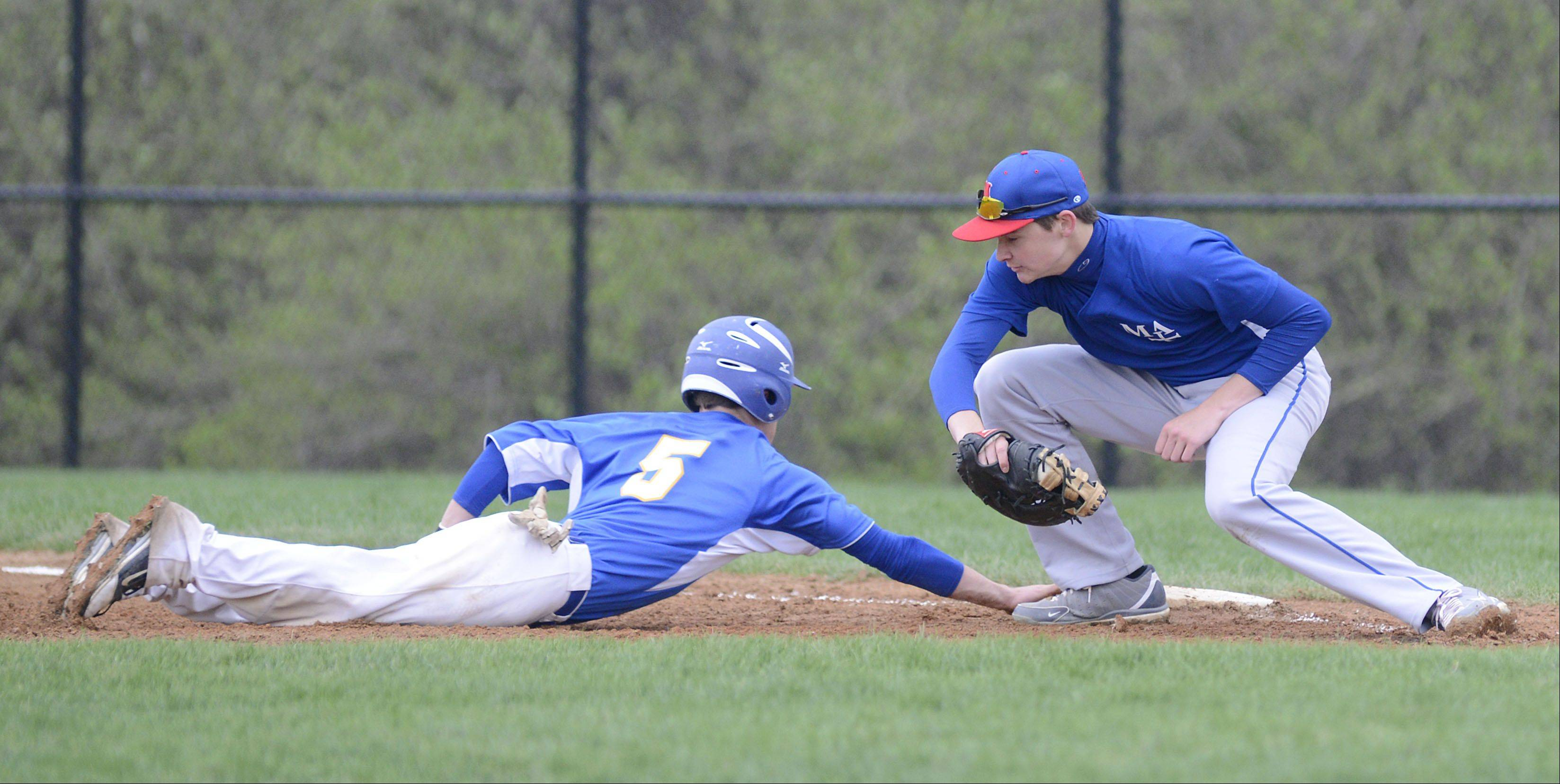 Aurora Central's Mike Fidler is safe back on first base with a slide from Marmion's Alex Troop in the second inning on Thursday, May 2.