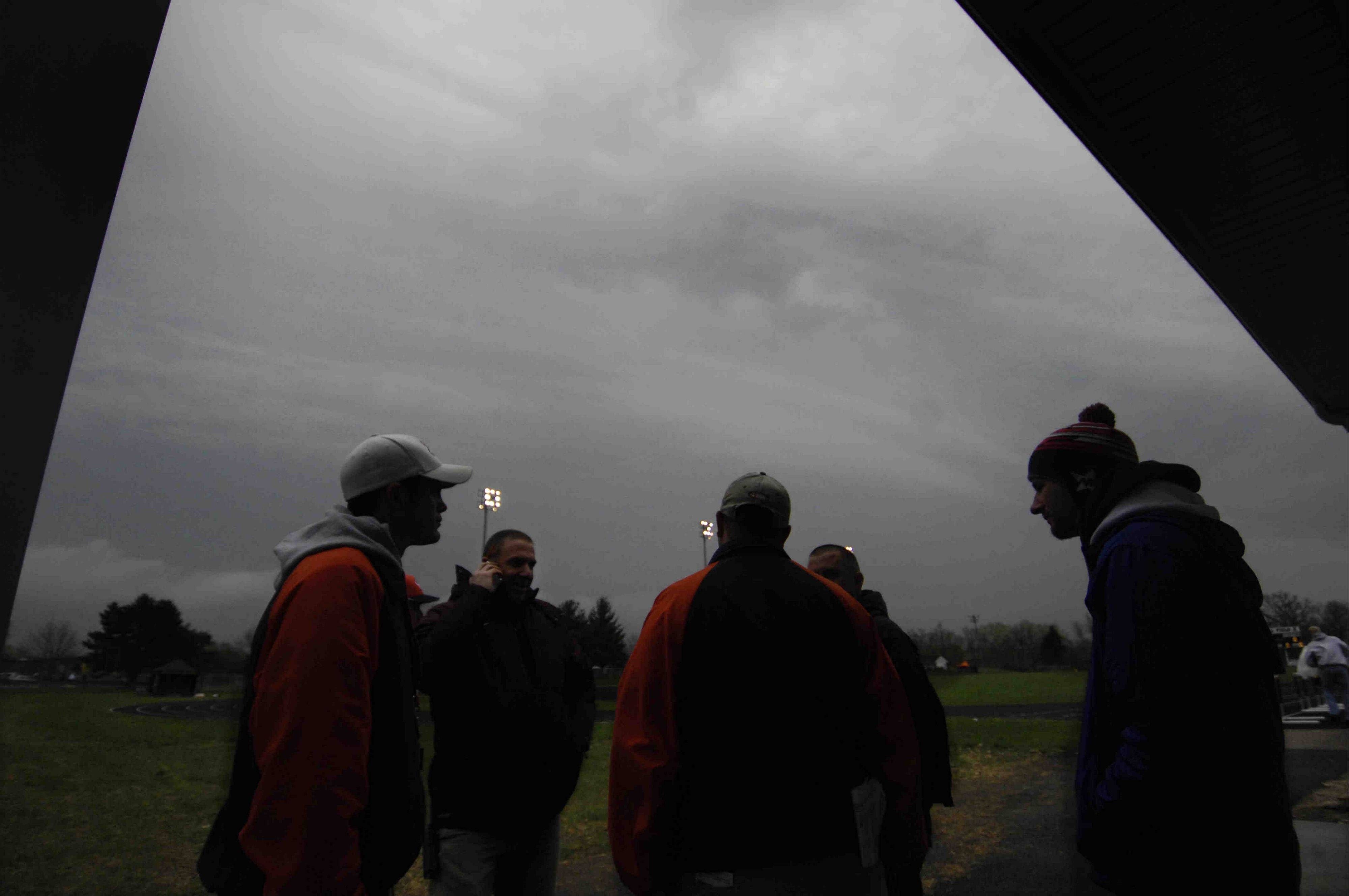 Elgin Athletic Director Paul Pennington, second from left, talks on the phone under ominous clouds as coaches gather to make a decision about trying to continue after more than one weather delay Thursday at the Upstate Eight Conference girls track meet at Memorial Field at Elgin High School.