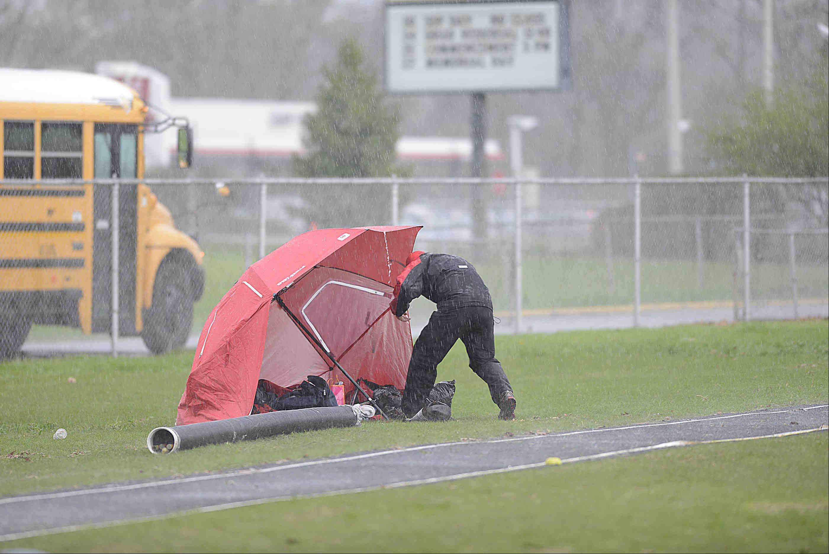 A coach gathers gear in the heavy rain Thursday at the Upstate Eight Conference girls track meet at Memorial Field at Elgin High School.