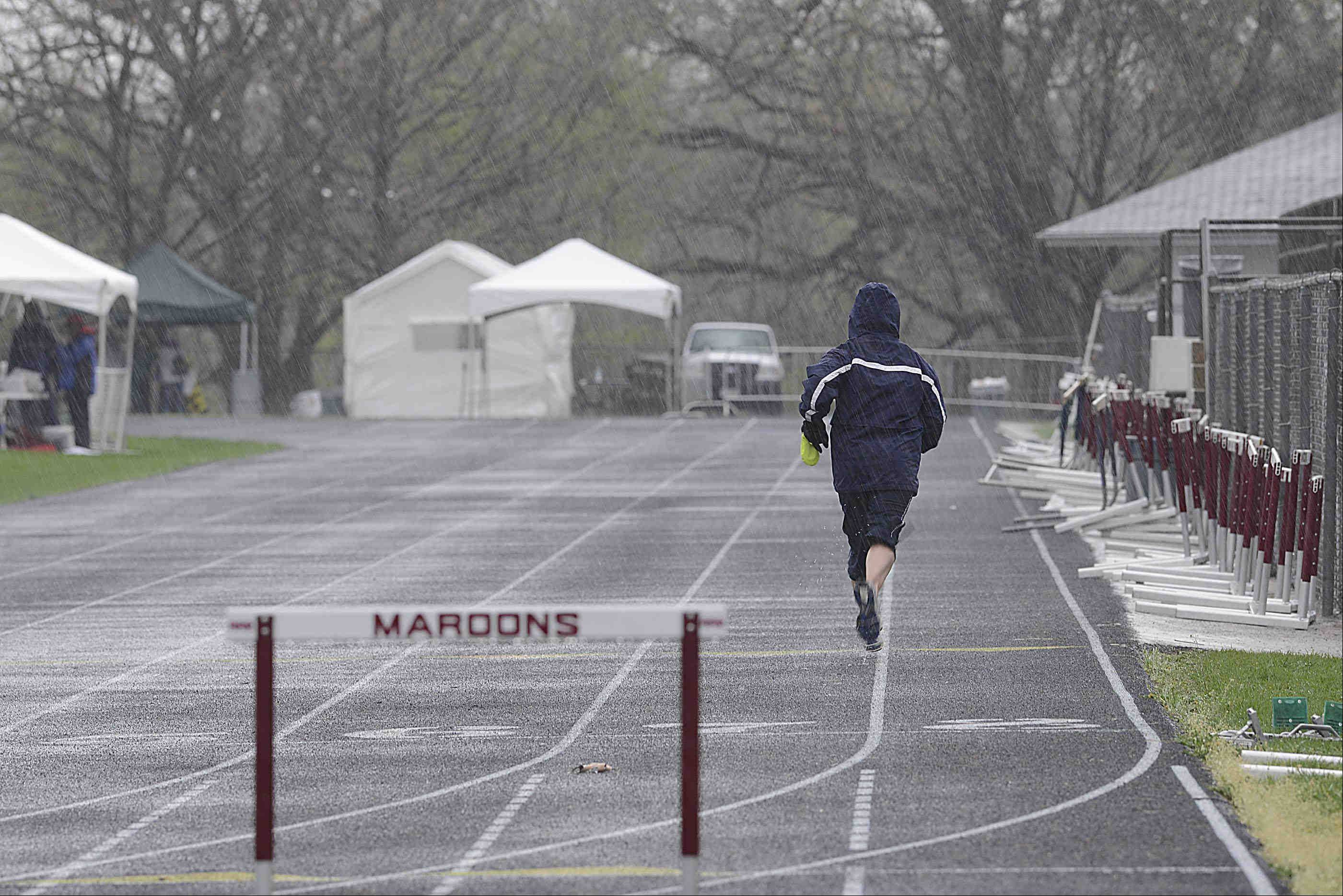 A coach runs to collect gear Thursday in the rain during a weather delay at the Upstate Eight Conference girls track meet at Memorial Field at Elgin High School.