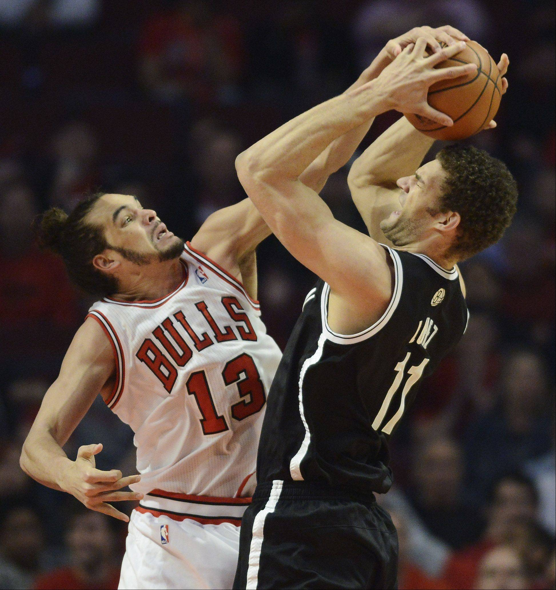 Joakim Noah of the Chicago Bulls ties up Brook Lopez of the Brooklyn Nets during the first quarter in Game 6 of the first round playoff game at the United Center in Chicago, Thursday, May 2, 2013.