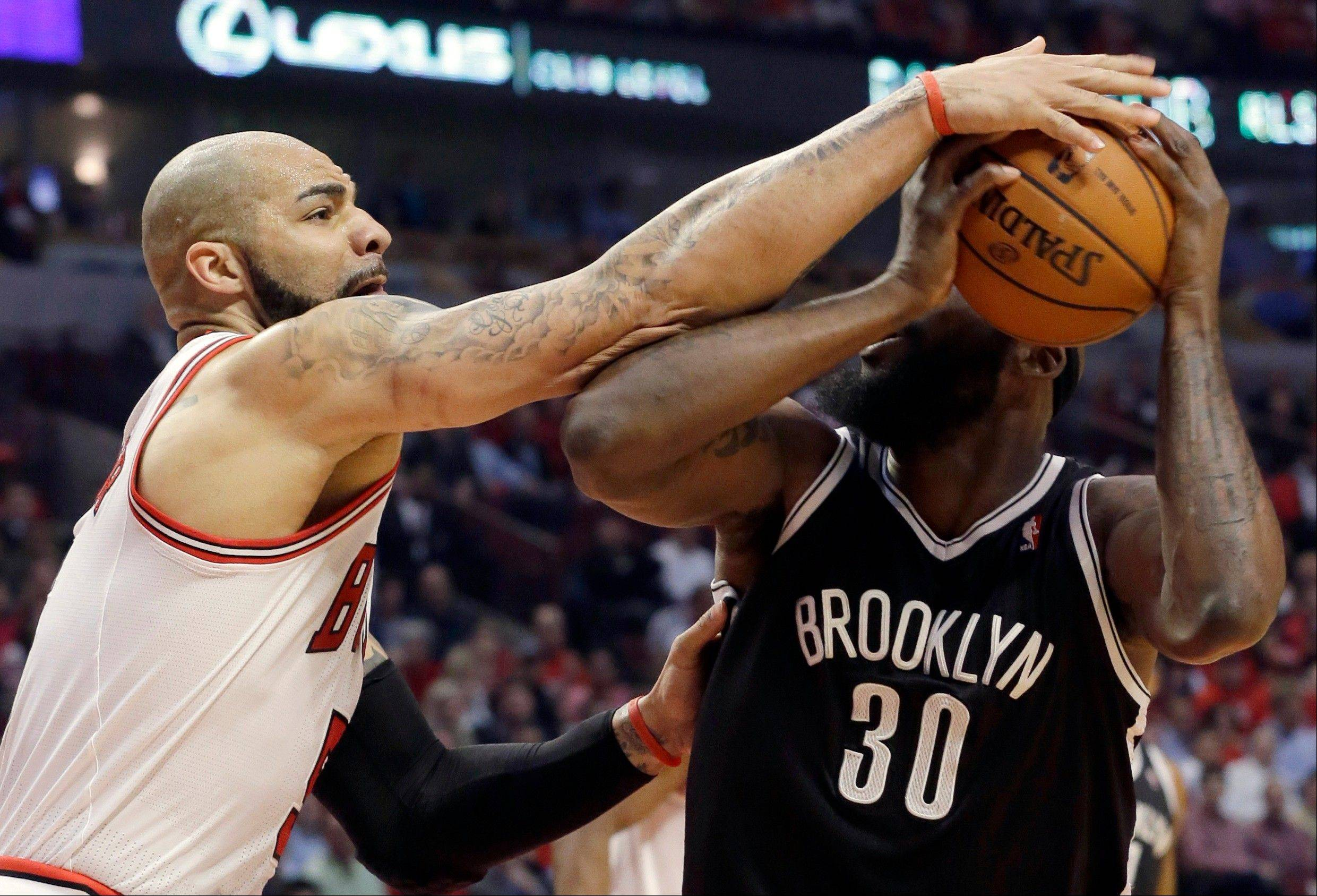 Chicago Bulls forward Carlos Boozer, left, defends against Brooklyn Nets forward Reggie Evans during the first half in Game 6 of their first-round NBA basketball playoff series in Chicago, Thursday, May 2, 2013.