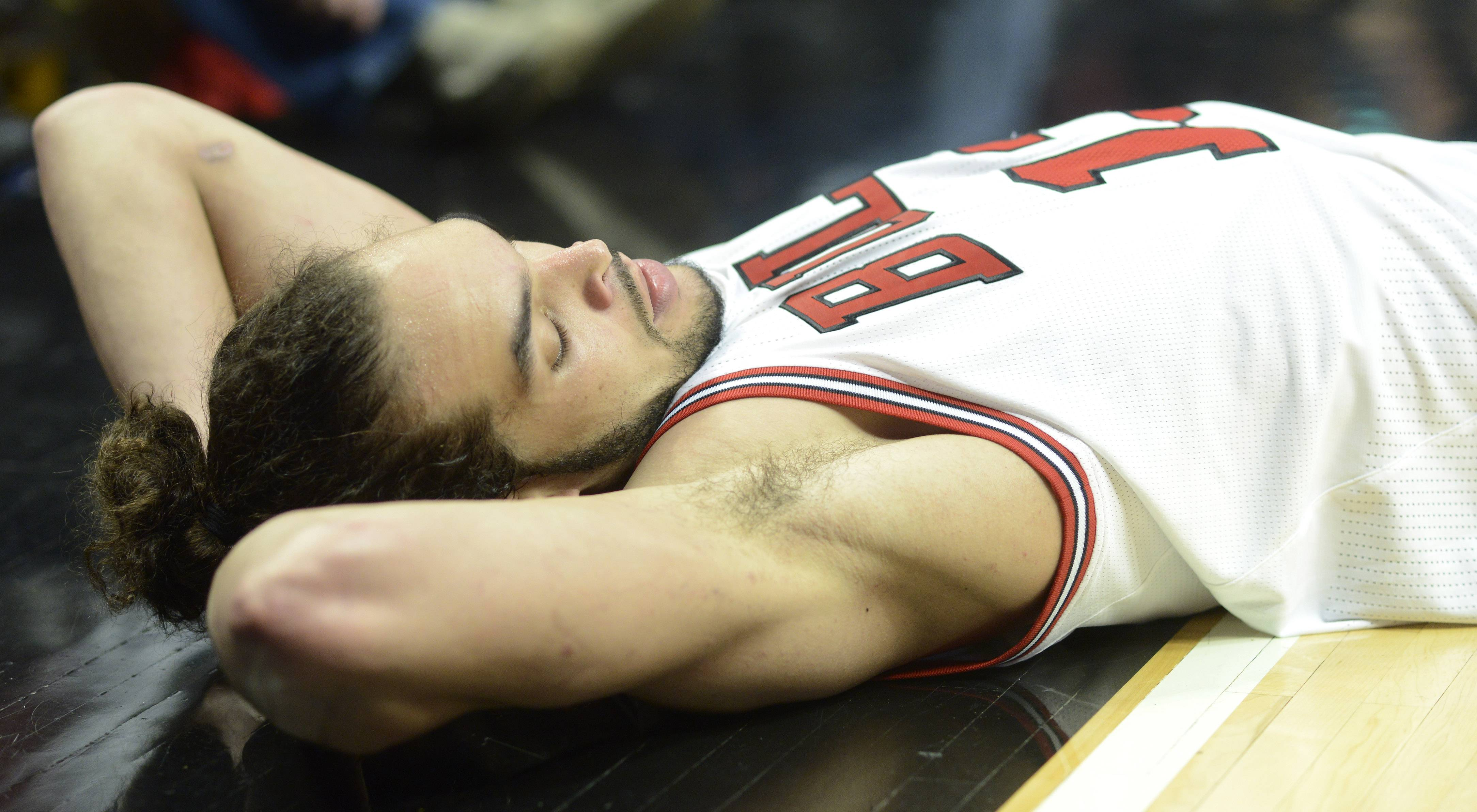 Joakim Noah of the Chicago Bulls lays on the floor in frustration after hustling for the ball, but passing it out-of-bounds in Game 6 of the first round playoff game against the Brooklyn Nets at the United Center in Chicago, Thursday, May 2, 2013.