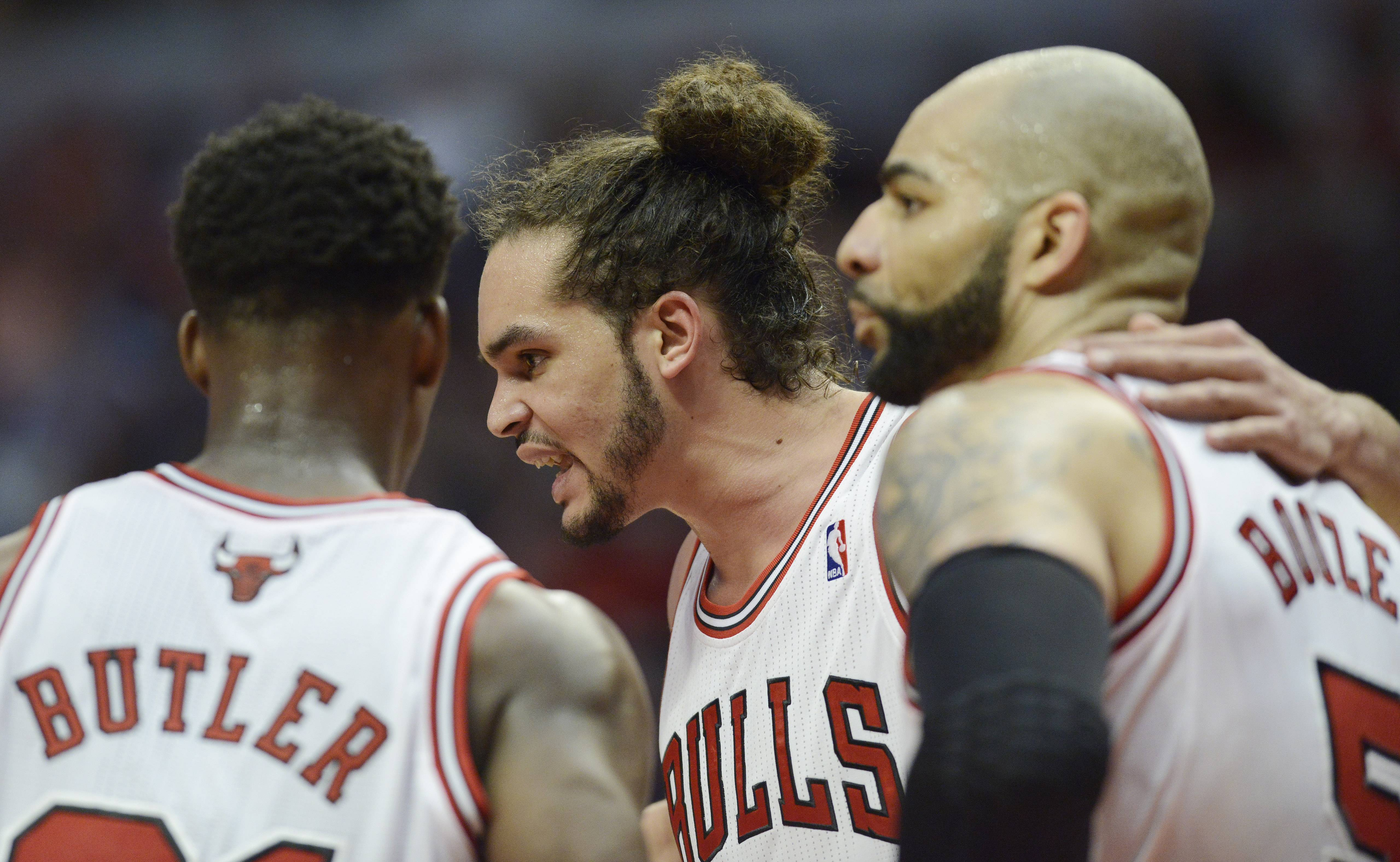 Joakim Noah, middle, talks to teammates Jimmy Butler, left, and Carlos Boozer in Game 6 of the first round playoff game against the Brooklyn Nets at the United Center in Chicago, Thursday, May 2, 2013.