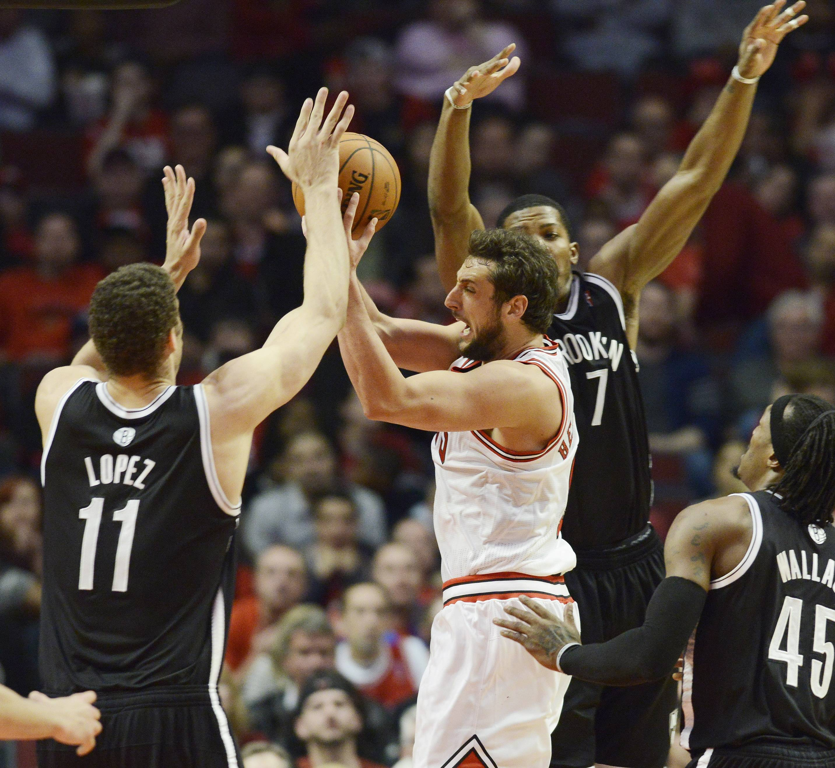 Marco Belinelli of the Chicago Bulls drives hard to the basket against Brook Lopez, left, and Deron Williams of the Brooklyn Nets in Game 6 of the first round playoff game at the United Center in Chicago, Thursday, May 2, 2013.
