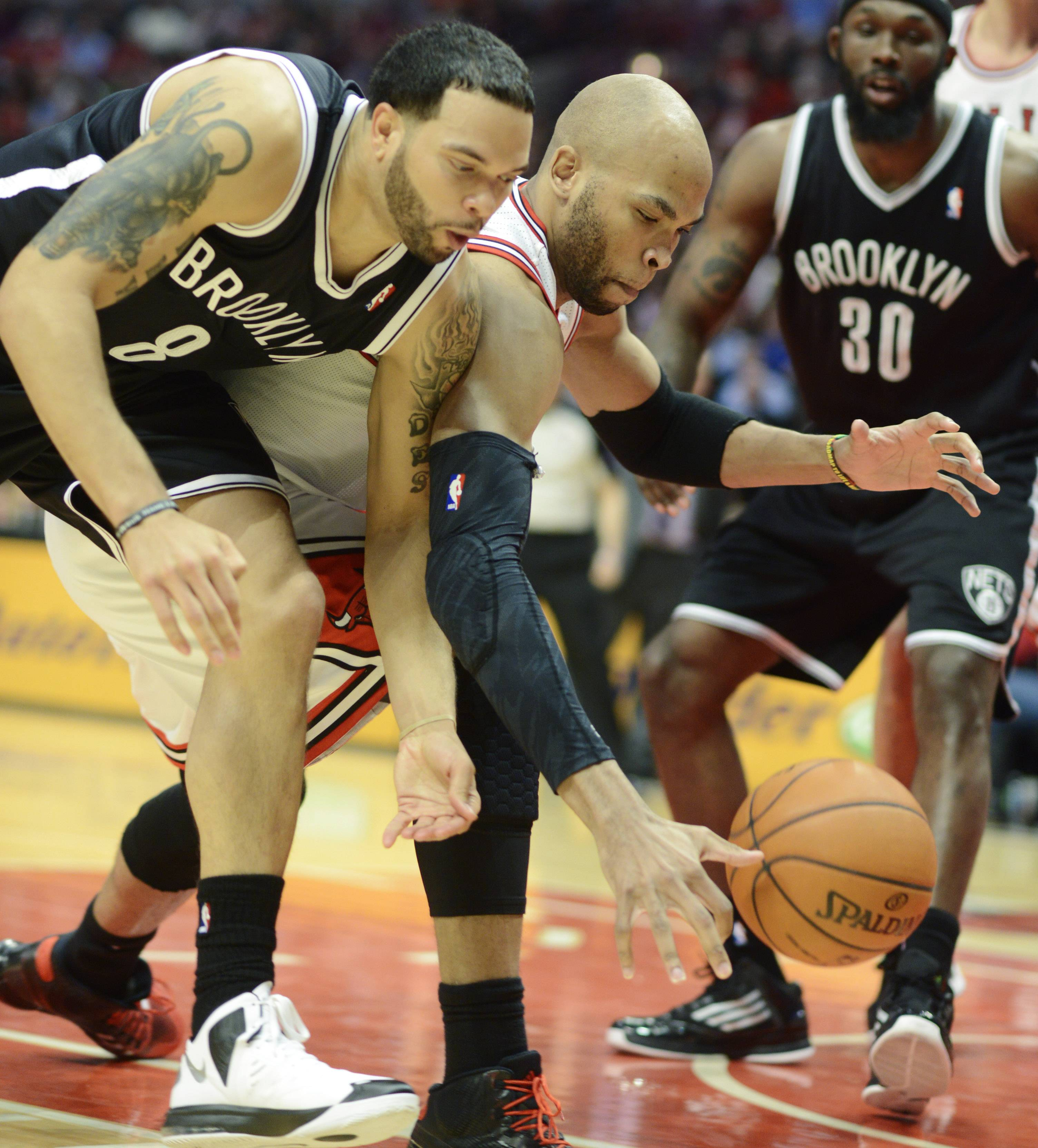 Deron Williams of the Brooklyn Nets, left, and Taj Gibson of the Chicago Bulls compete for a loose ball in Game 6 of the first round playoff game at the United Center in Chicago, Thursday, May 2, 2013.