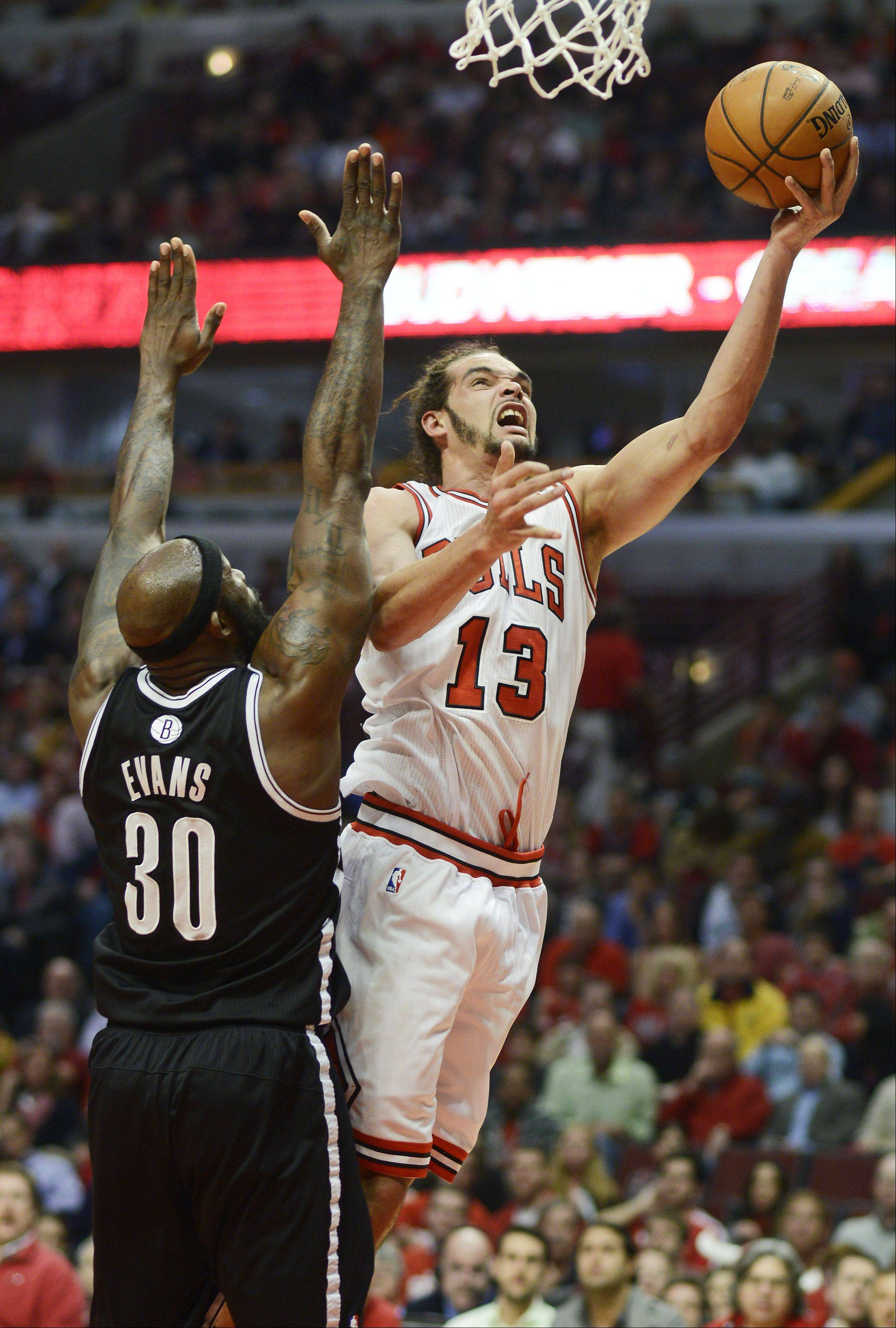 Joakim Noah of the Chicago Bulls drives to the basket for a layup against Brooklyn Nets defender Reggie Evans in Game 6 of the first round playoff game at the United Center in Chicago, Thursday, May 2, 2013.