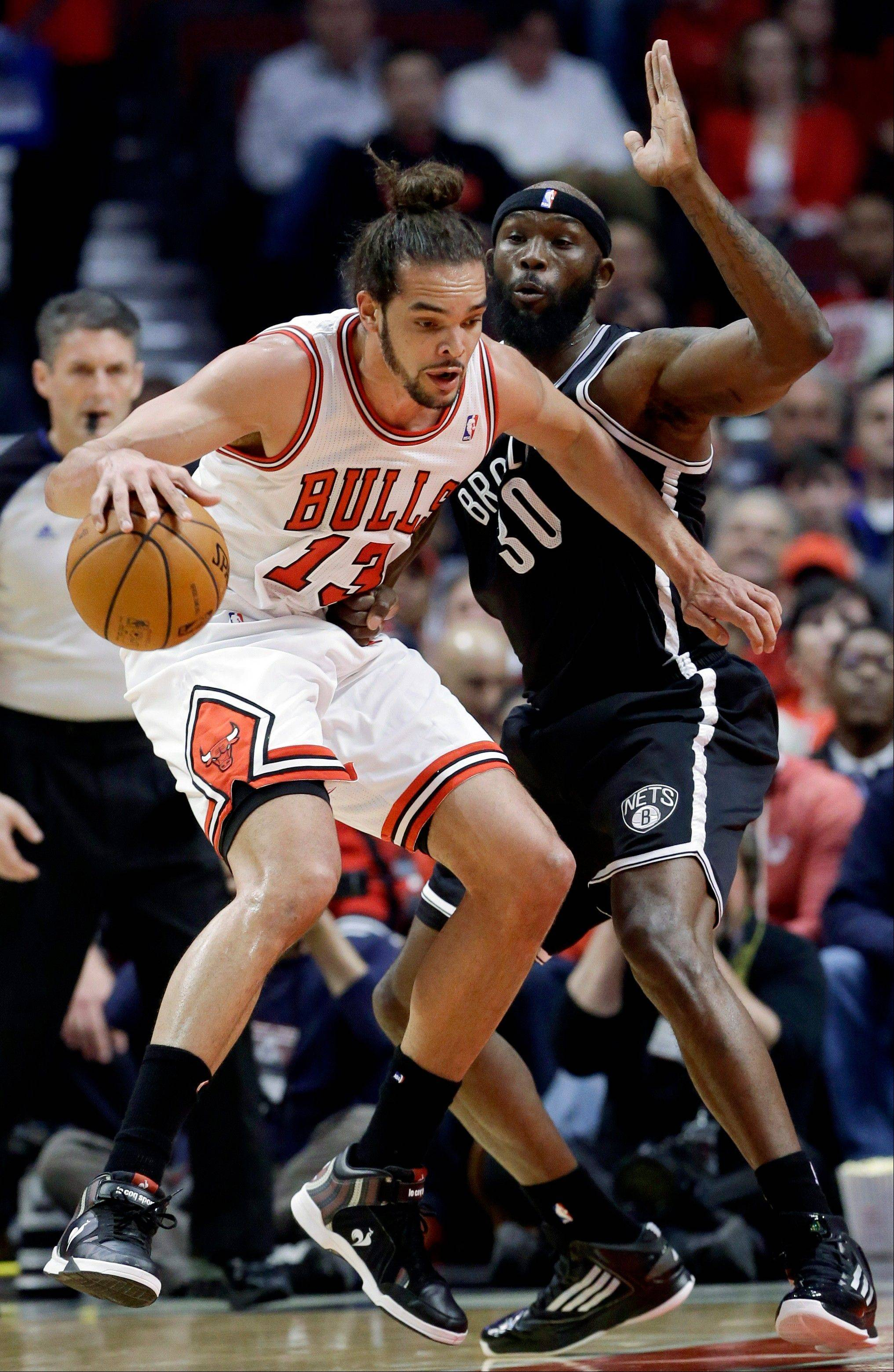 Chicago Bulls center Joakim Noah, left, drives against Brooklyn Nets forward Reggie Evans during the first half in Game 6 of their first-round NBA basketball playoff series in Chicago, Thursday, May 2, 2013.
