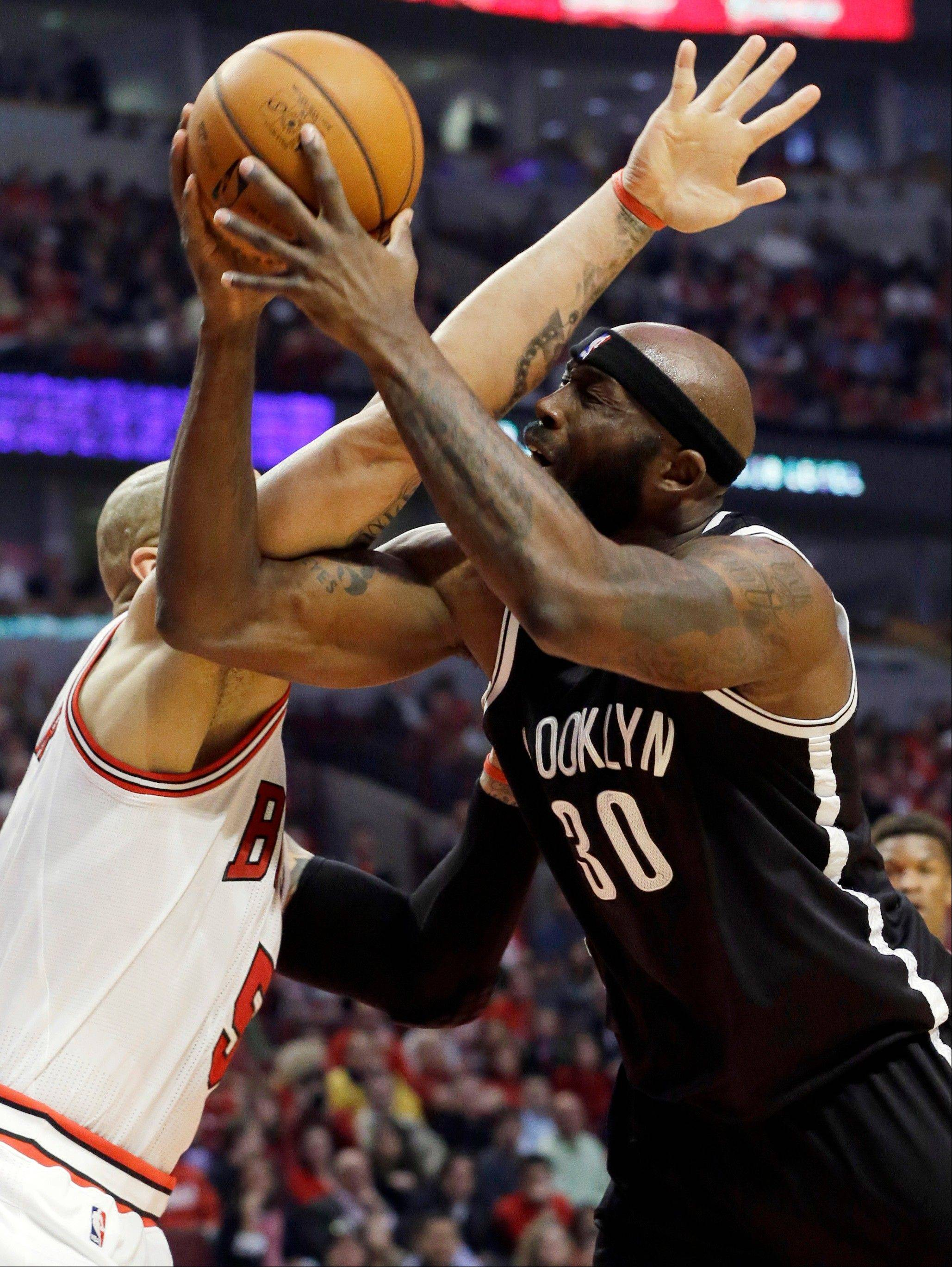 Brooklyn Nets forward Reggie Evans, right, shoots against Chicago Bulls forward Carlos Boozer during the first half in Game 6 of their first-round NBA basketball playoff series in Chicago, Thursday, May 2, 2013.