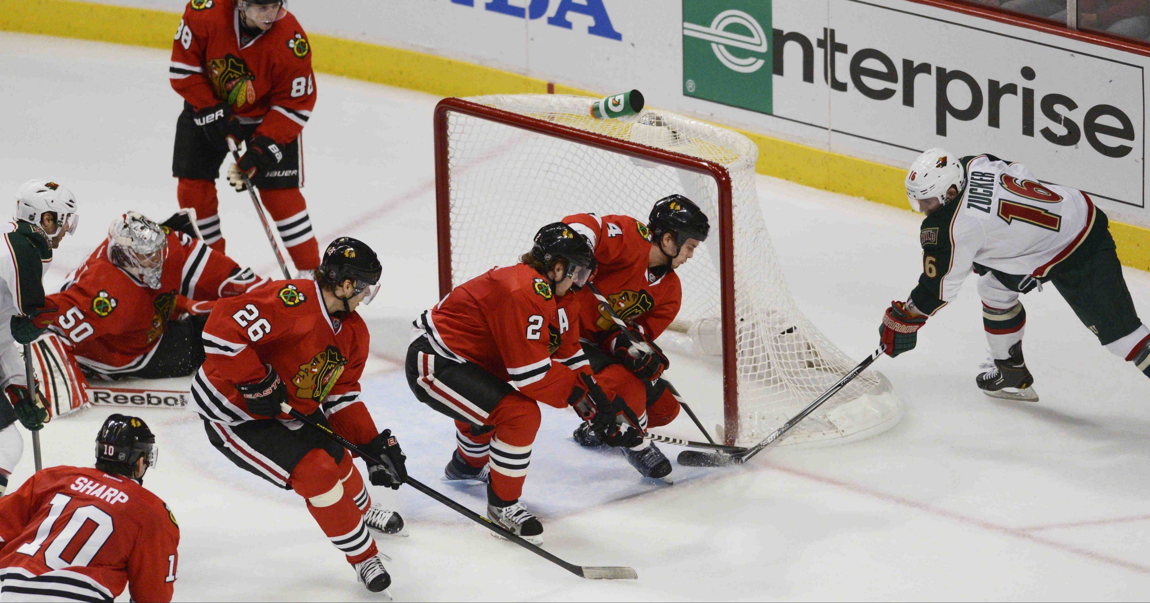 Niklas Hjalmarsson and Duncan Keith defend the goal against Minnesota left wing Jason Zucker as goalie Corey Crawford scrambled back into position Tuesday in Game 1 of the Western Conference first-round playoff series.