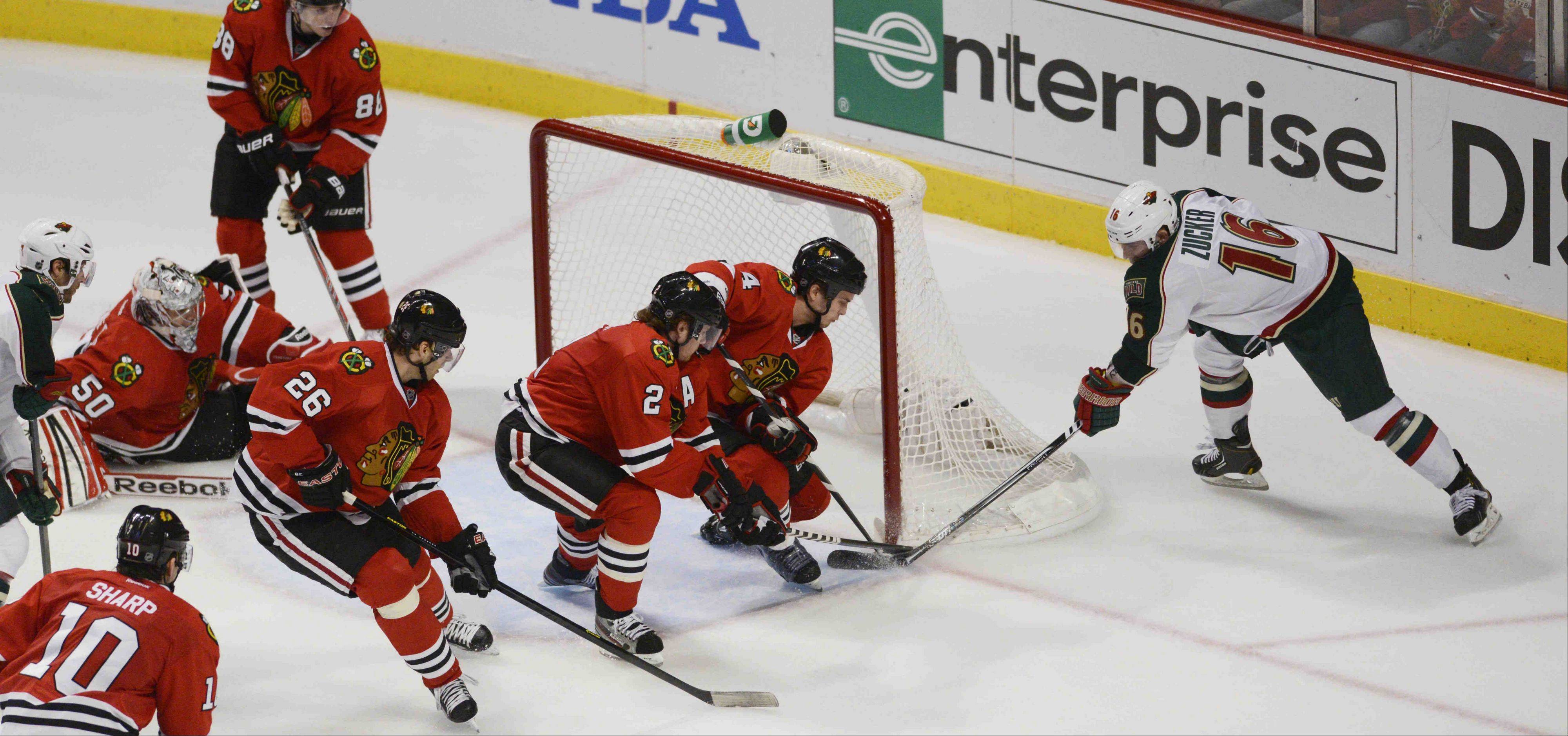 Chicago Blackhawks defenseman Niklas Hjalmarsson and defenseman Duncan Keith defend the goal against Minnesota left wing Jason Zucker as goalie Corey Crawford scrambled back into position Tuesday in Game 1 of the Western Conference first-round playoff series.