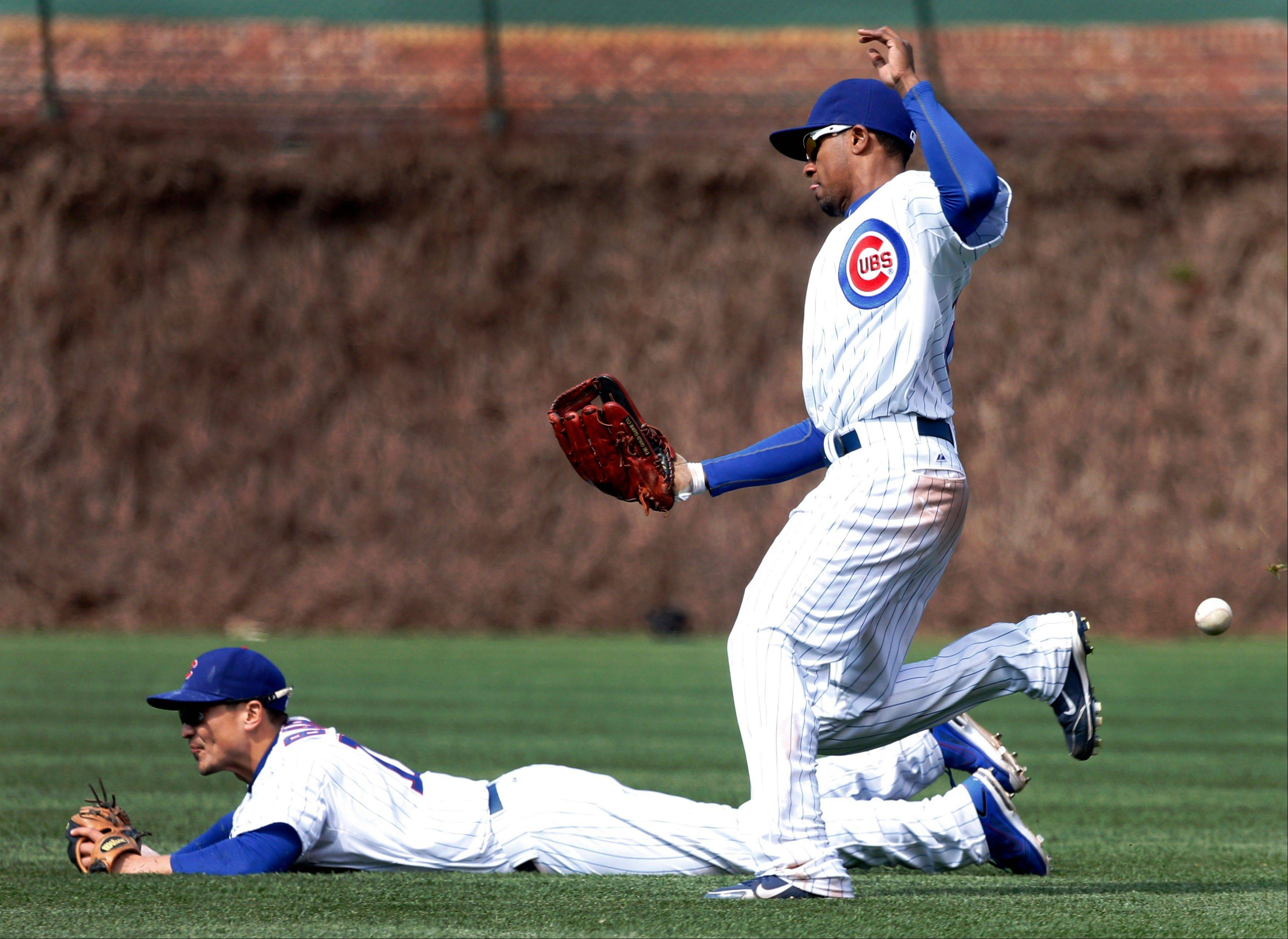 Chicago Cubs right fielder Julio Borbon, right, is unable to catch a shallow pop fly off the bat of San Diego Padres' Yonder Alonso, scoring Jesus Guzman, as second baseman Darwin Barney falls to the turf during the eighth inning of a baseball game Thursday, May 2, 2013, in Chicago.