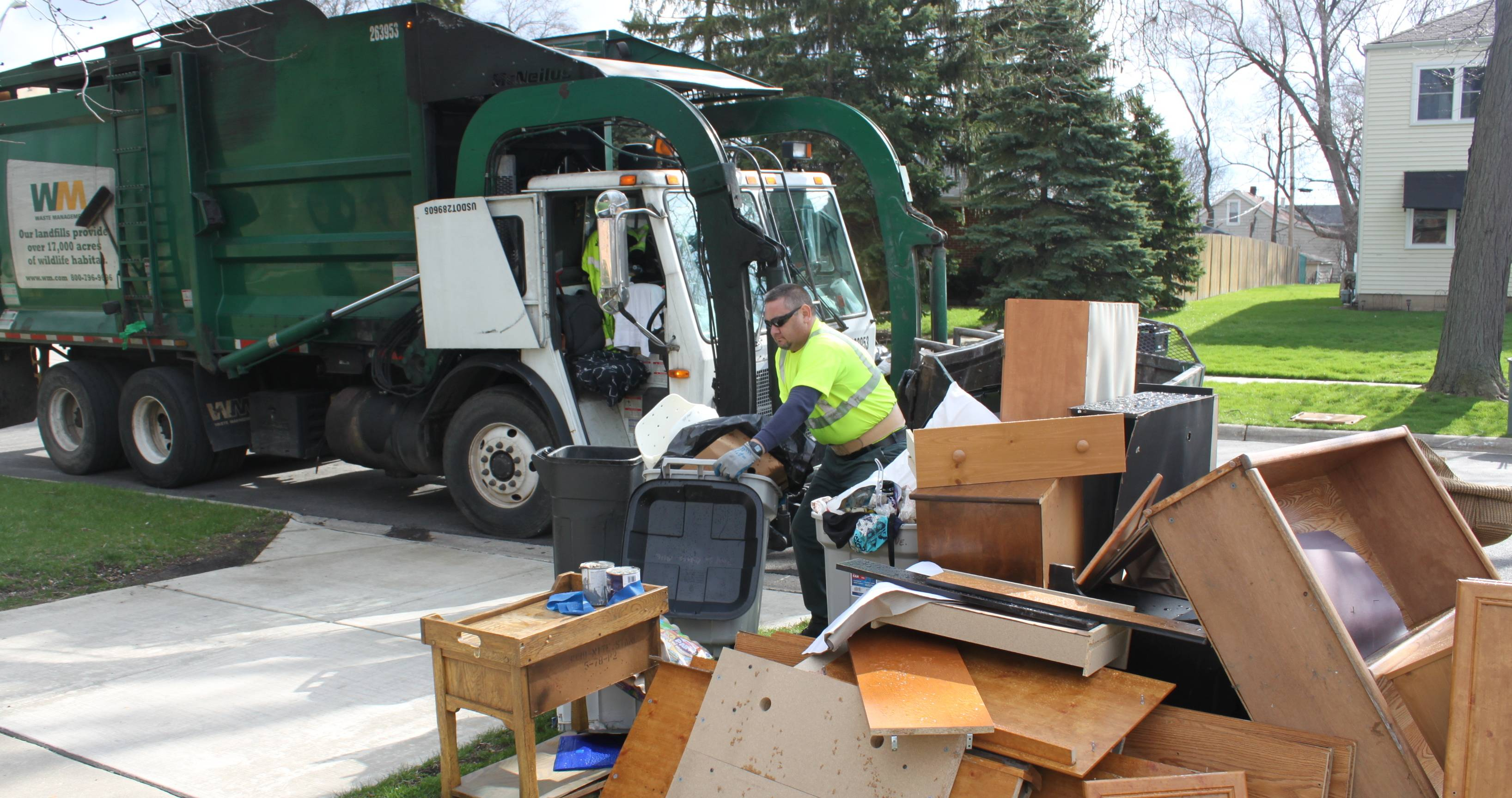 Waste Management driver Alfredo Sanchez hauls away  damaged furniture after heavy rains flooded basements in Lombard.