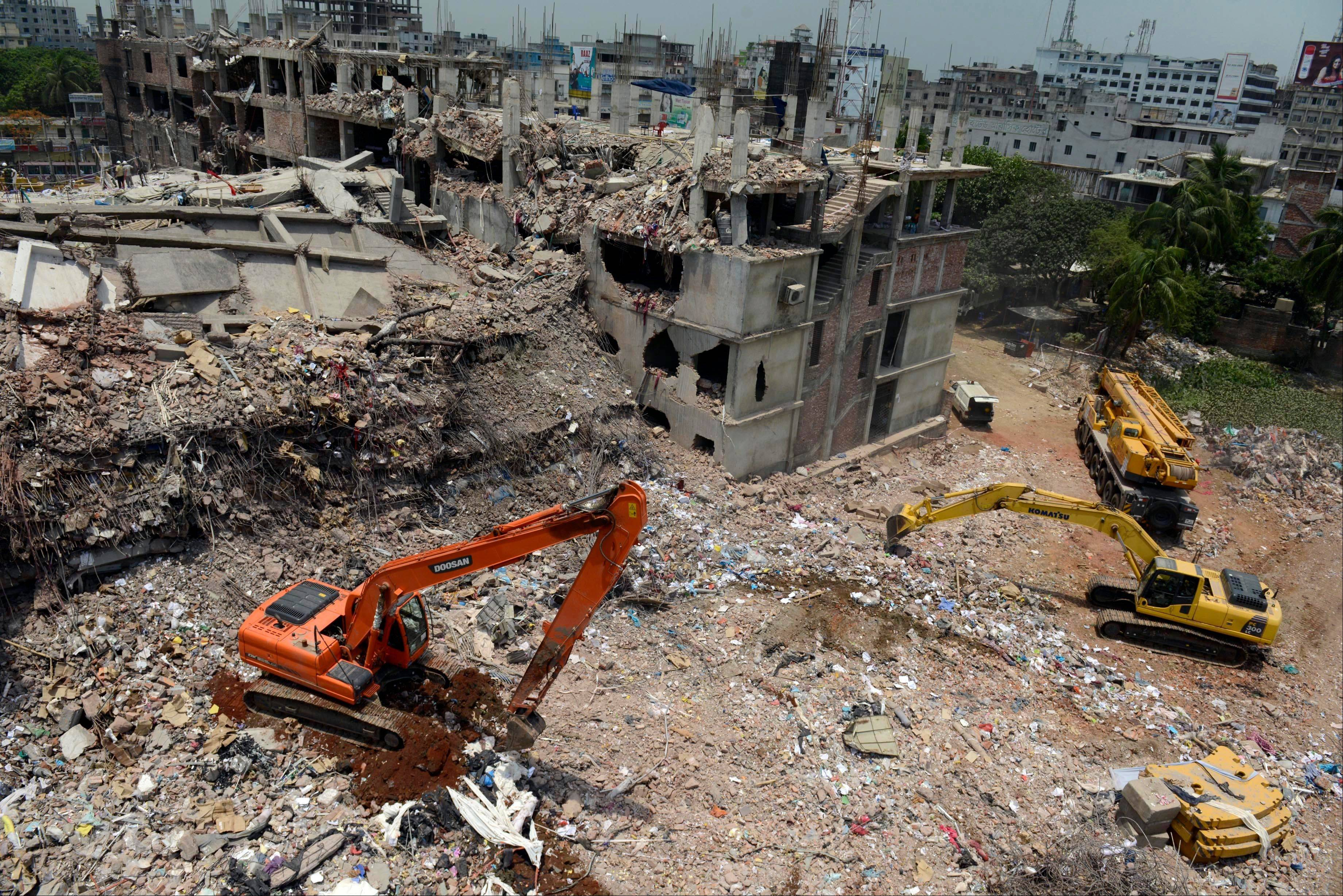 Earth movers work to remove rubble at the site of a garments factory that collapsed in Savar near Dhaka, Bangladesh, Friday, May 3, 2013. More than 500 bodies have been recovered from the debris of the building.