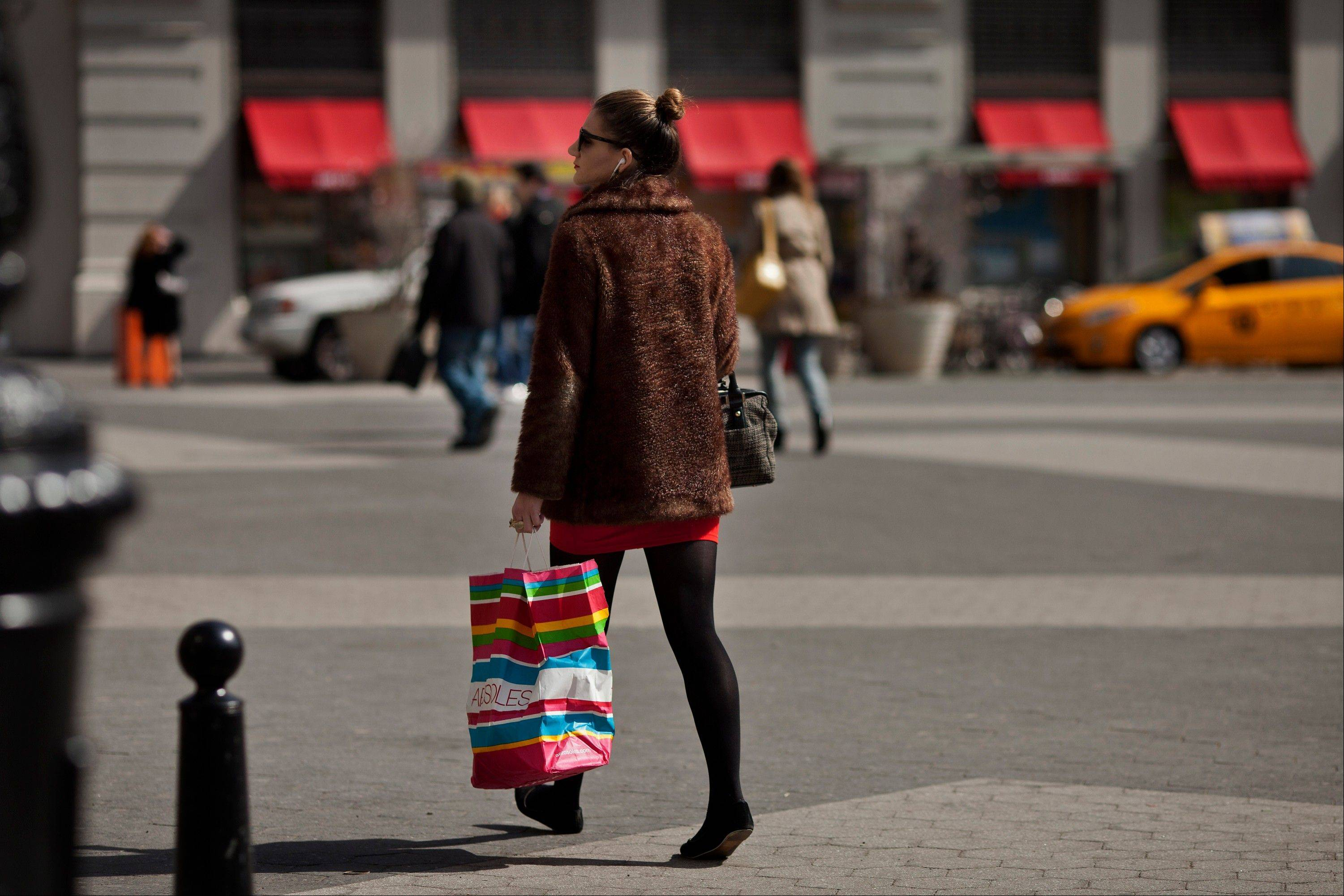 A woman carries an Aerosoles shopping bag while walking through Union Square in New York, U.S., on Thursday, April 4, 2013. Confidence among U.S. consumers stabilized last week, stemming a pullback in sentiment that had threatened to check recent gains in spending.