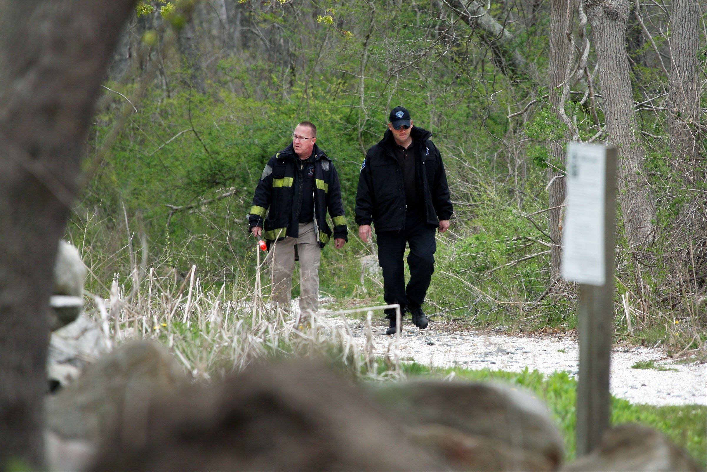 Massachusetts State Police walk out of the woods of The Smith Neck Farm Friday in Dartmouth, Mass.